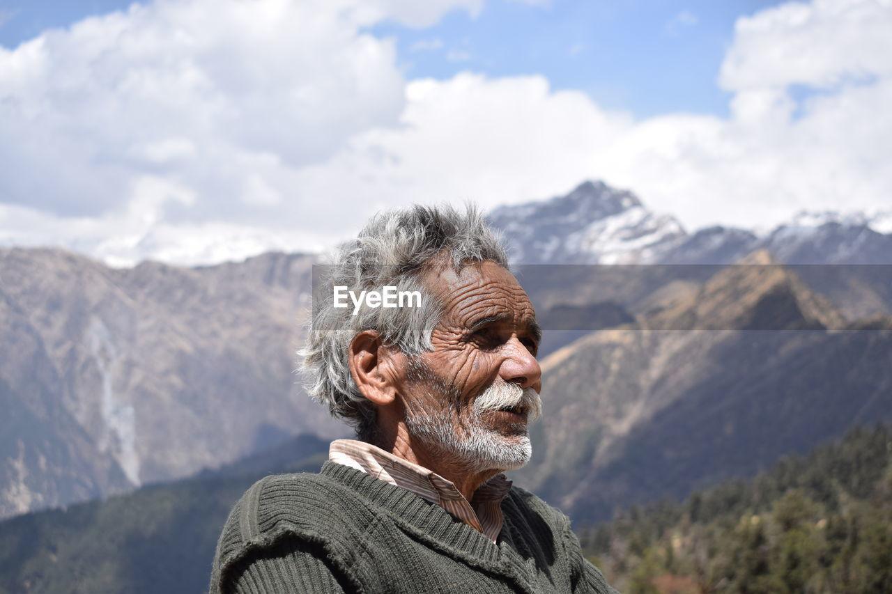 Senior Man Standing Against Mountain