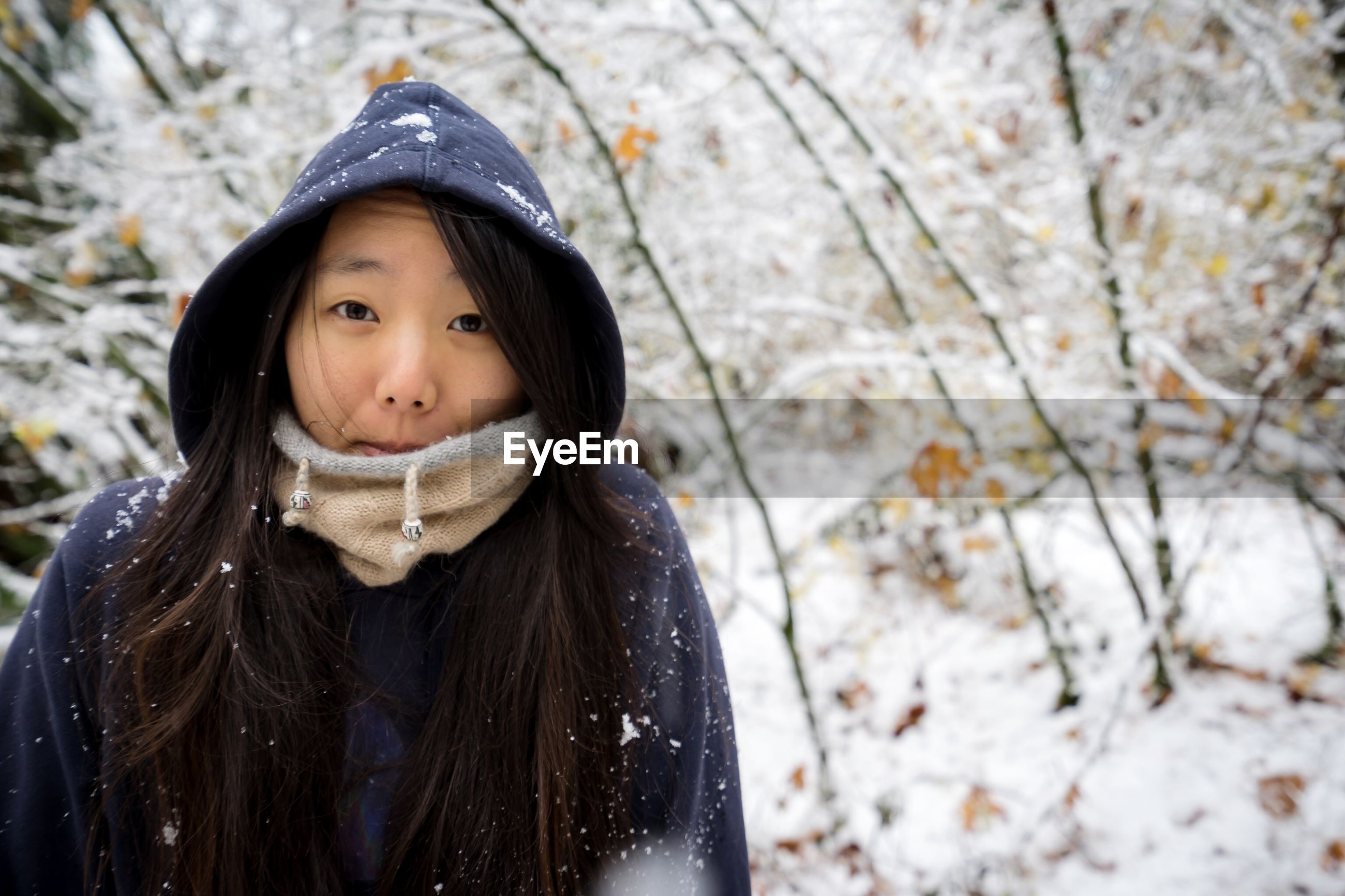Portrait of woman wearing hood while standing in snow