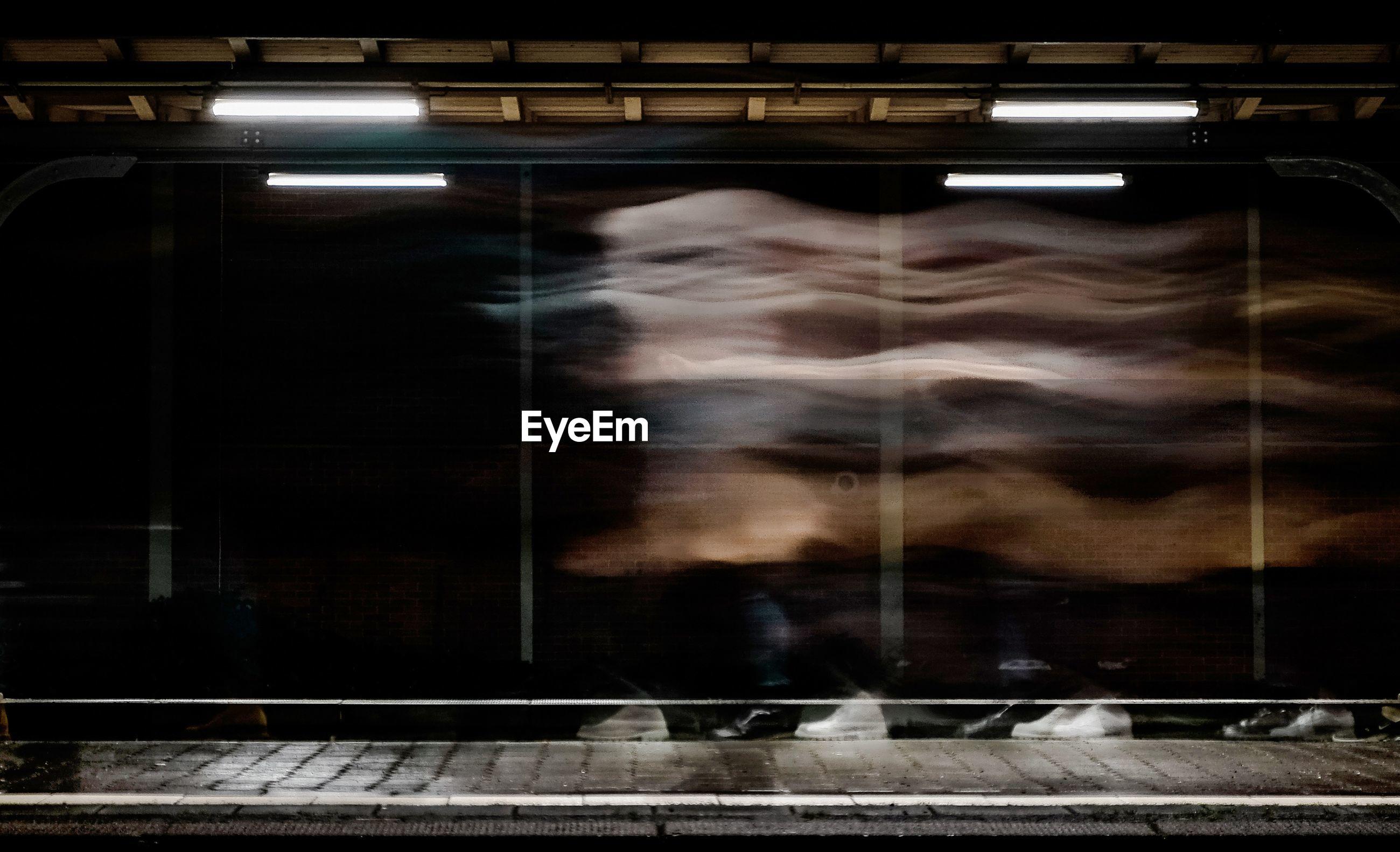 REFLECTION OF WOMAN ON RAILROAD STATION PLATFORM SEEN THROUGH WINDOW