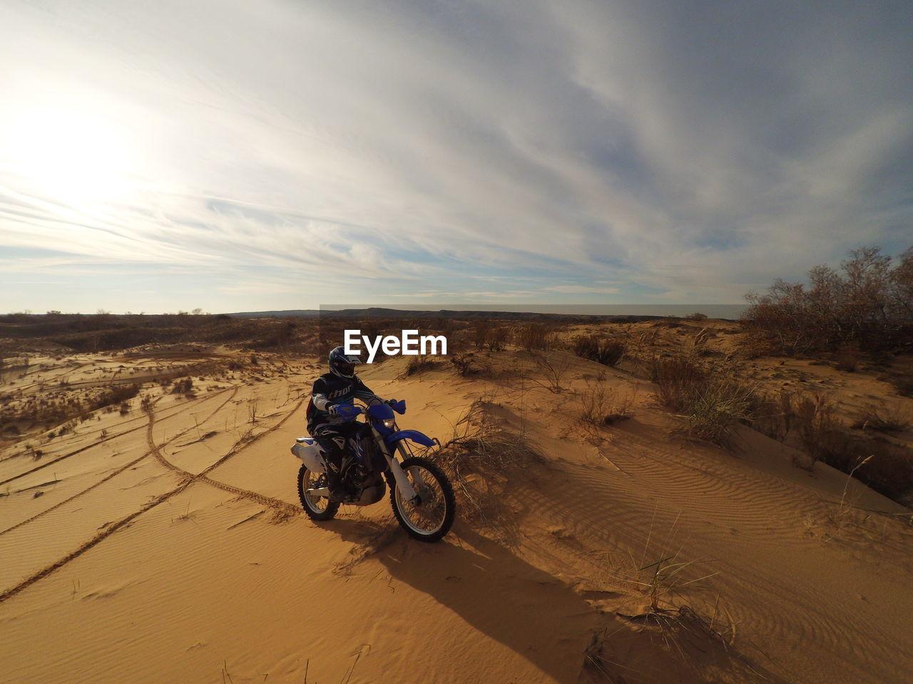 MAN RIDING BICYCLE ON SAND AT DESERT