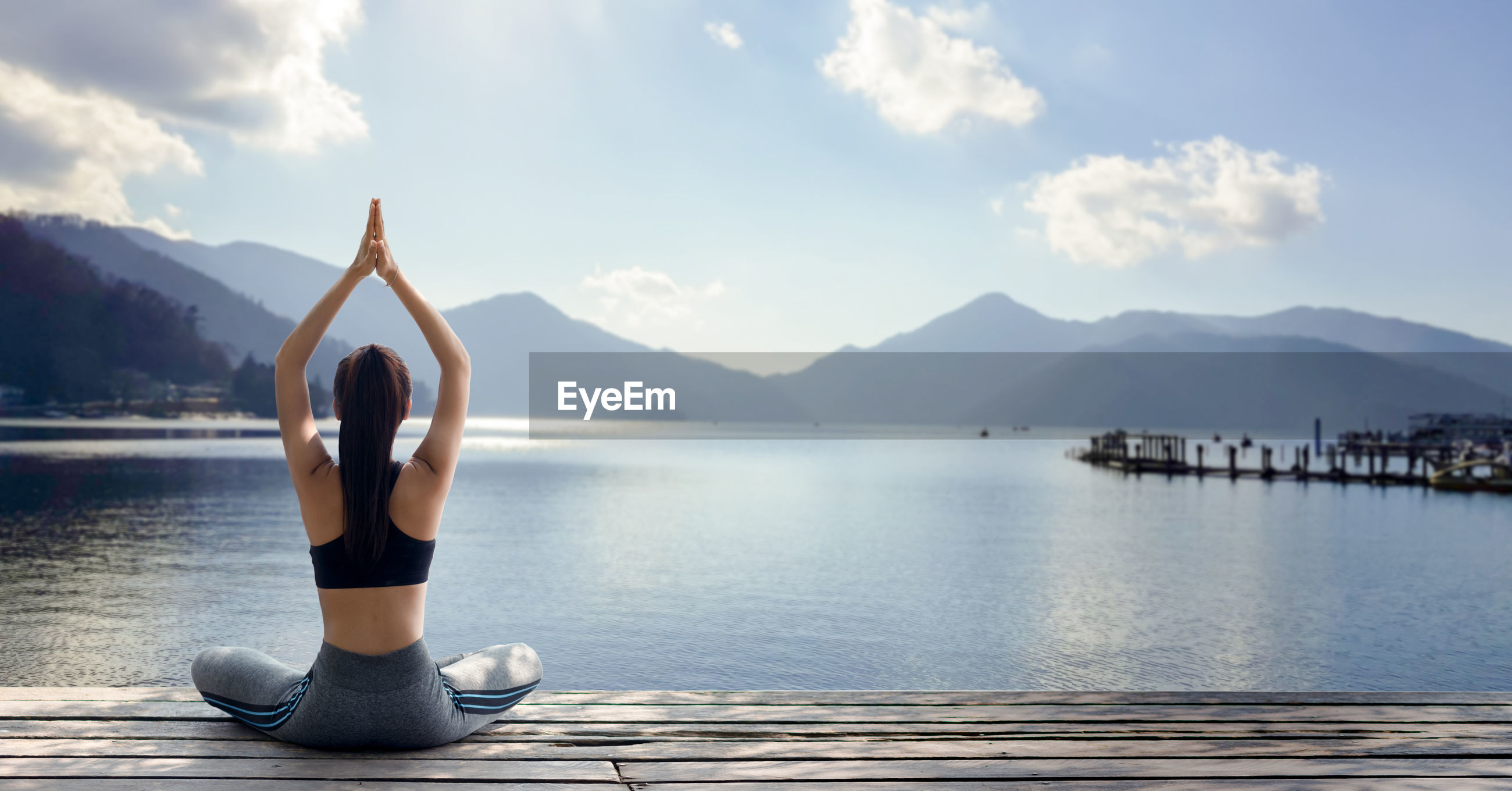 Rear view of woman with arms raised meditating by lake