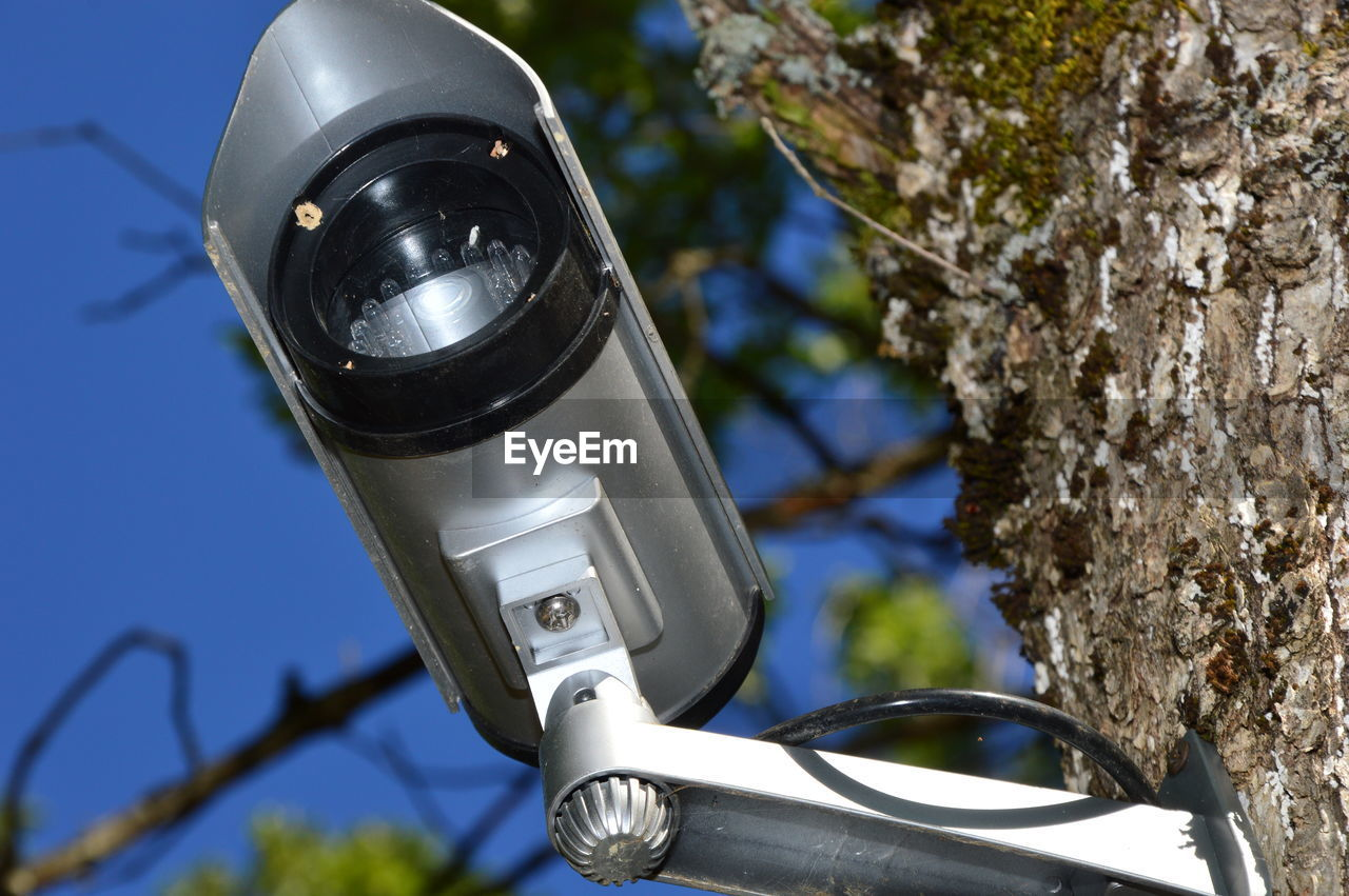 CLOSE-UP OF COIN-OPERATED BINOCULARS AGAINST TREES