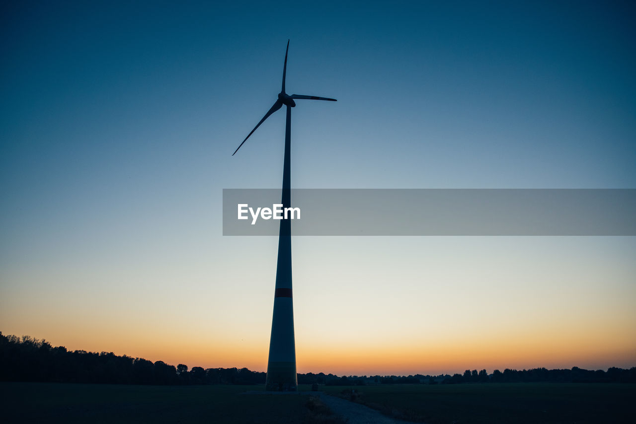 Wind Turbine On Field Against Clear Blue Sky