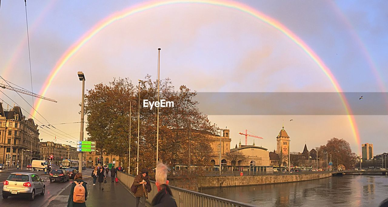 rainbow, architecture, building exterior, built structure, double rainbow, sky, city, cloud - sky, real people, city life, outdoors, day, multi colored, lifestyles, nature, large group of people, bubble wand, people