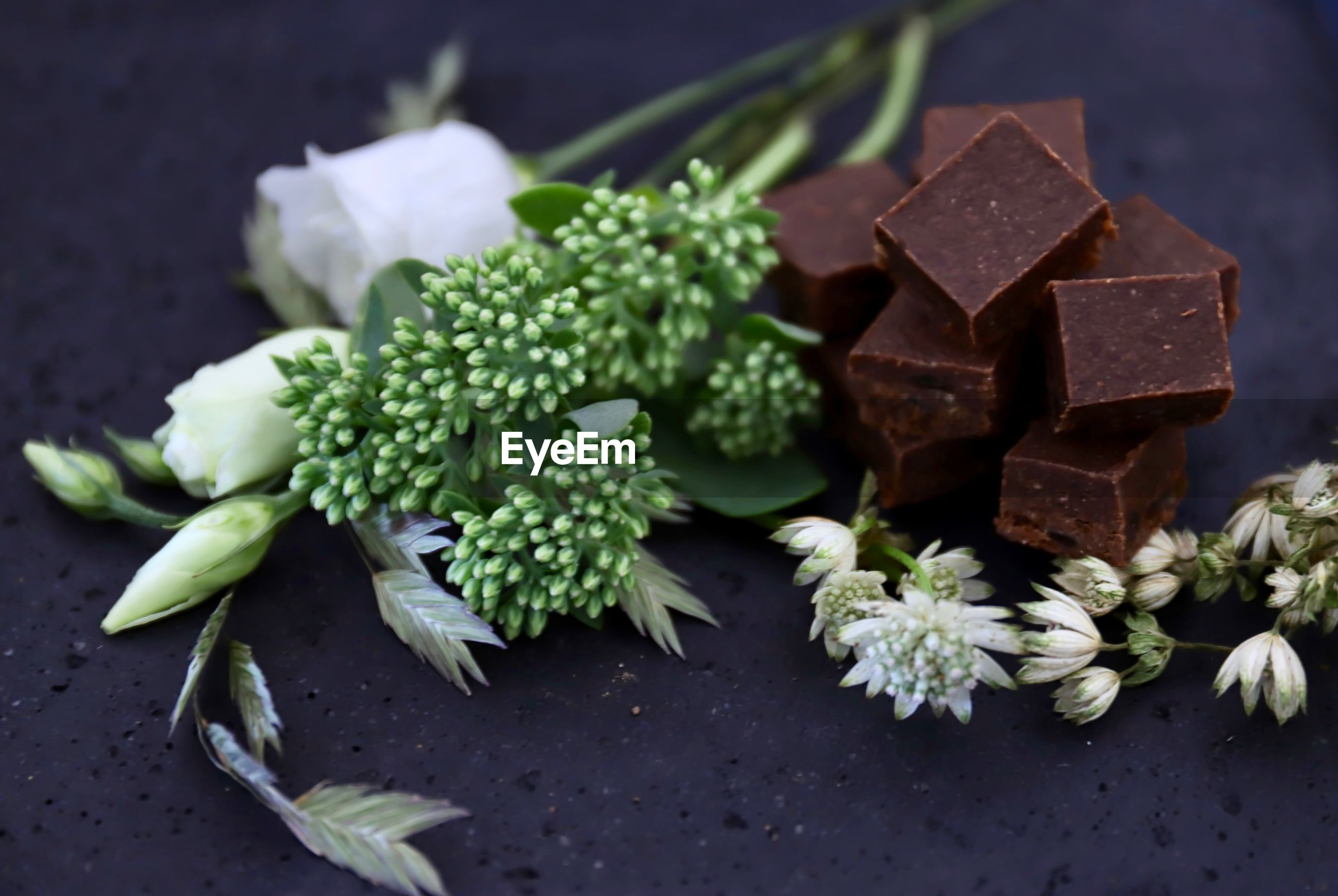 Close-up of chocolates by flowers on table