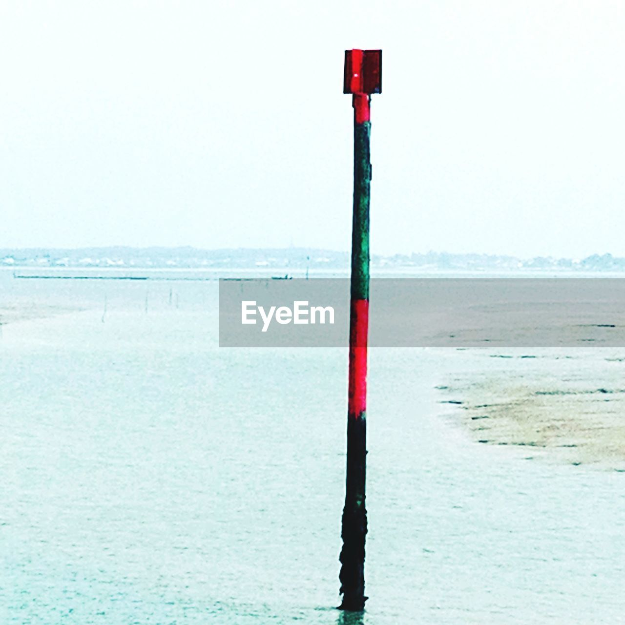 water, sea, sky, horizon, horizon over water, scenics - nature, pole, nature, beauty in nature, tranquility, beach, land, day, red, tranquil scene, no people, clear sky, outdoors, non-urban scene, wooden post