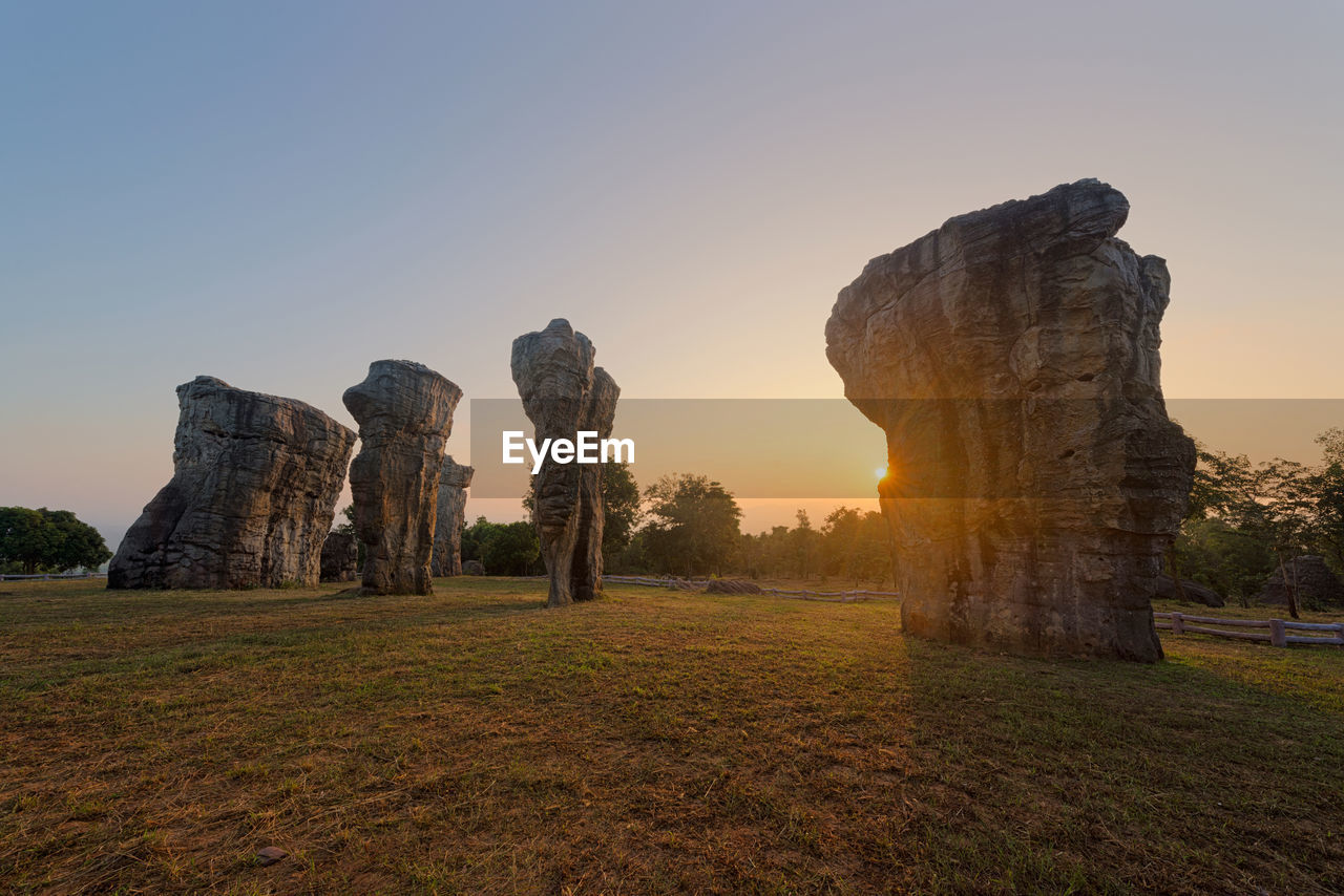 sky, sunset, nature, land, grass, ancient, no people, rock, environment, tranquility, history, solid, plant, field, rock formation, tranquil scene, beauty in nature, clear sky, sunlight, sun, archaeology, ancient civilization, outdoors, ruined
