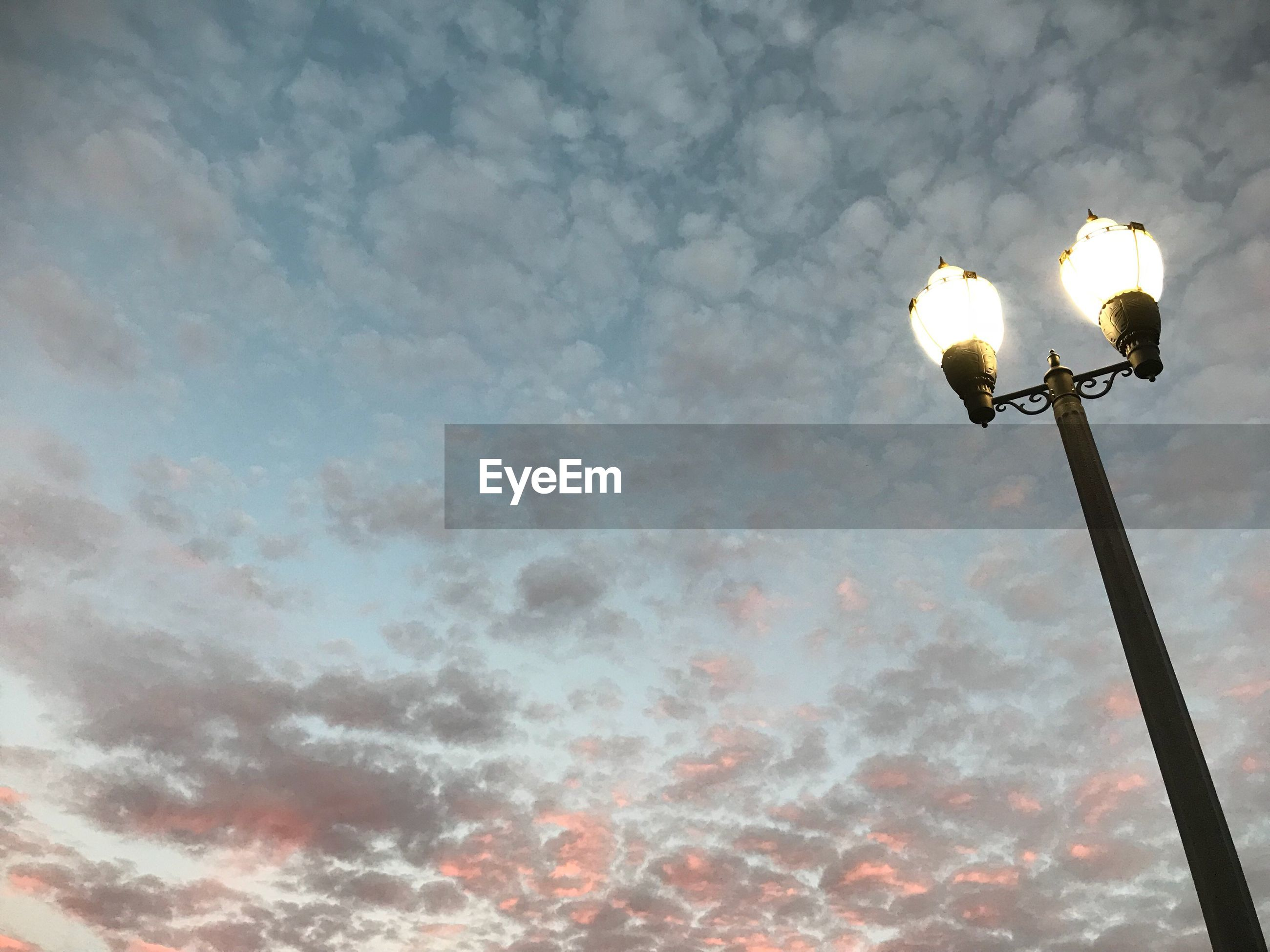 Low angle view of illuminated street light against sky during sunset