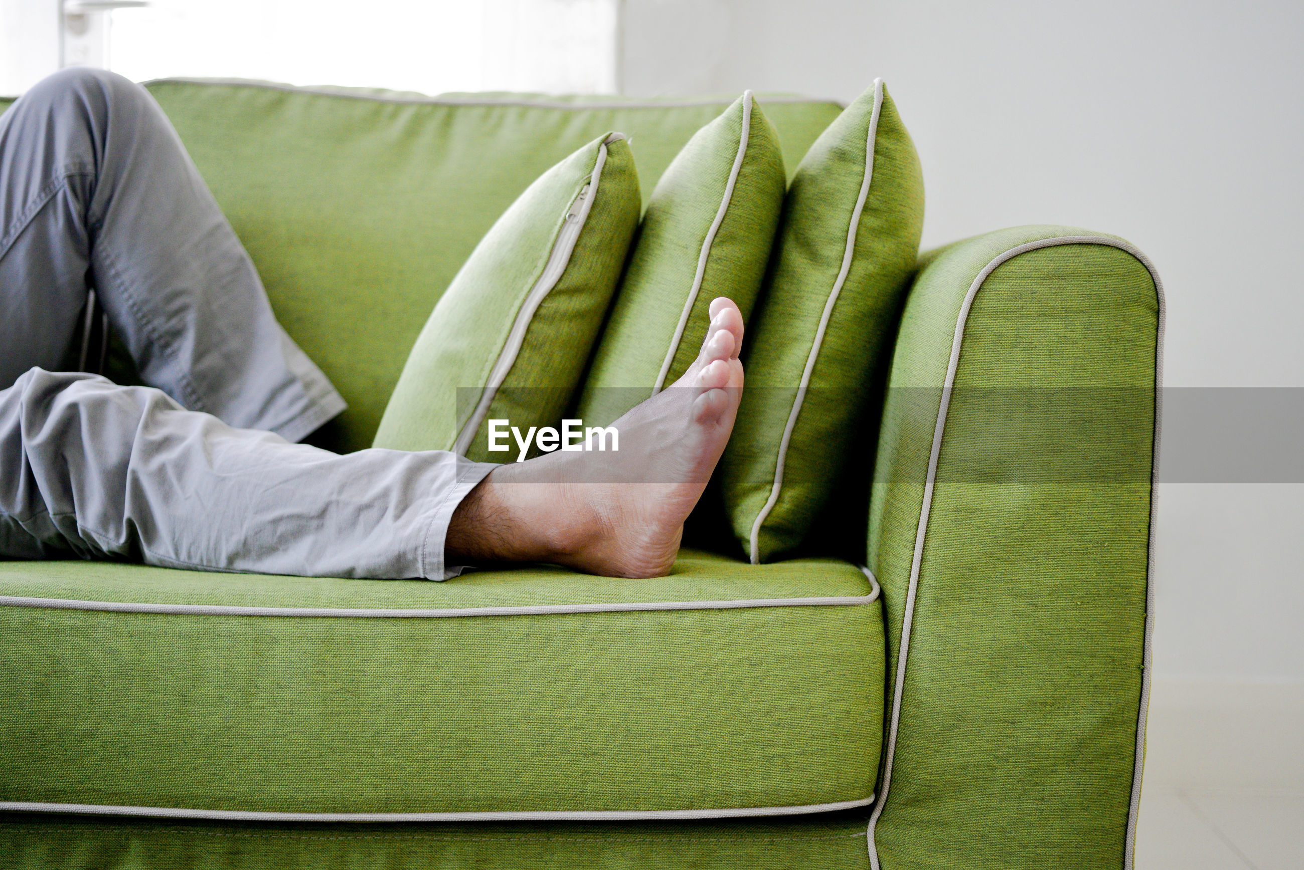 Low section of man sitting on sofa