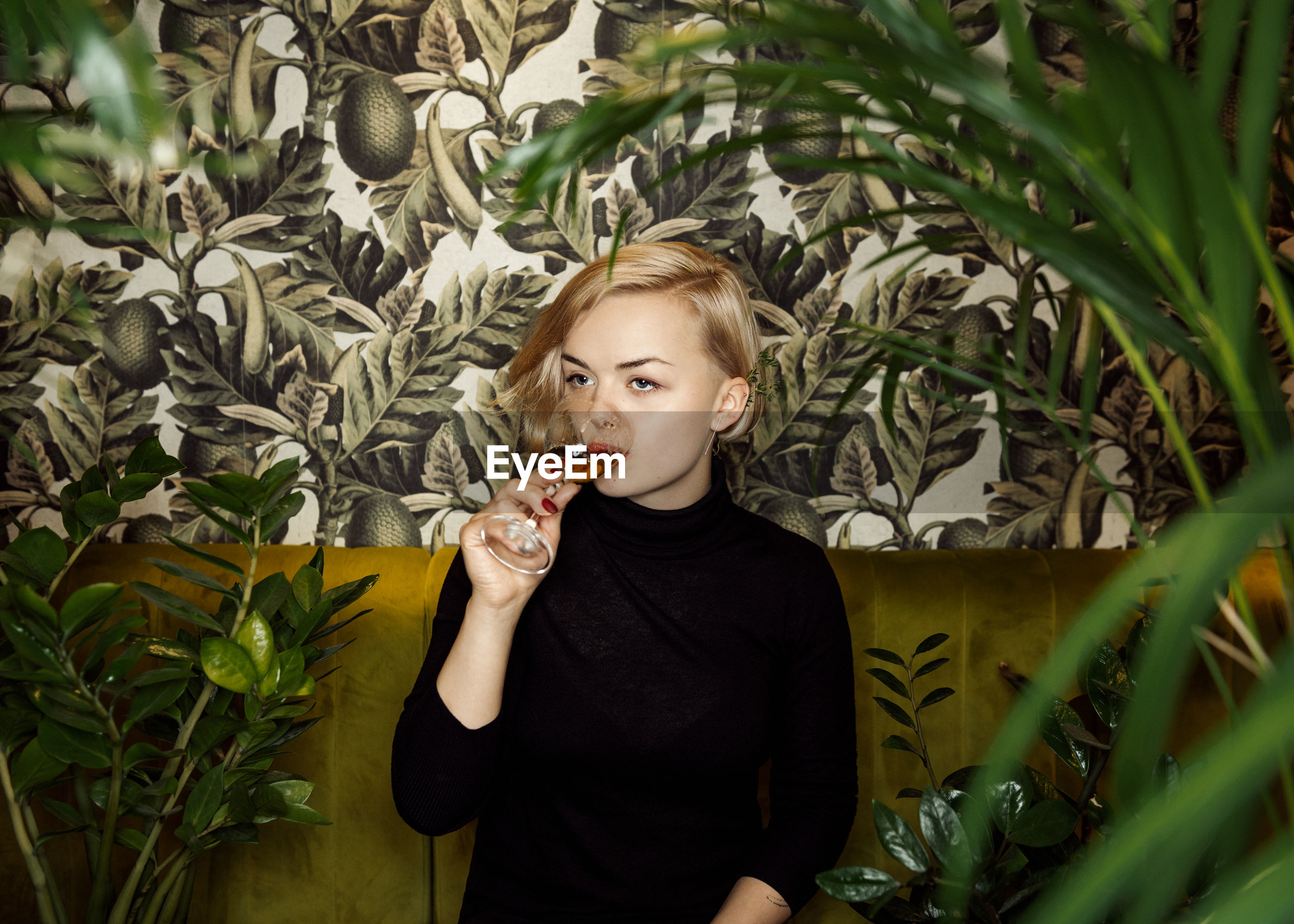 Young woman drinking drink while looking away by plants