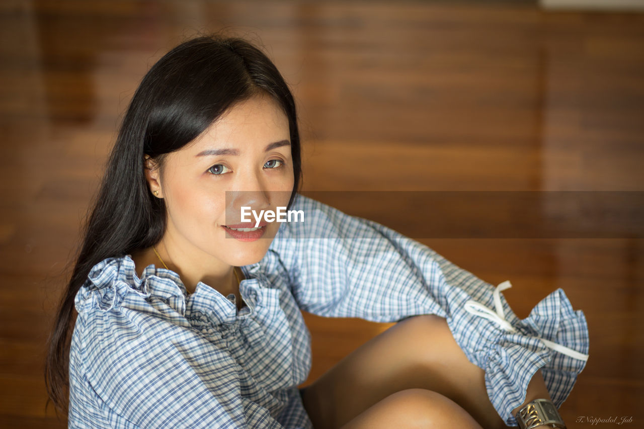 looking at camera, sitting, young women, young adult, real people, one person, beautiful woman, portrait, smiling, indoors, focus on foreground, sofa, home interior, casual clothing, relaxation, leisure activity, lifestyles, day, close-up