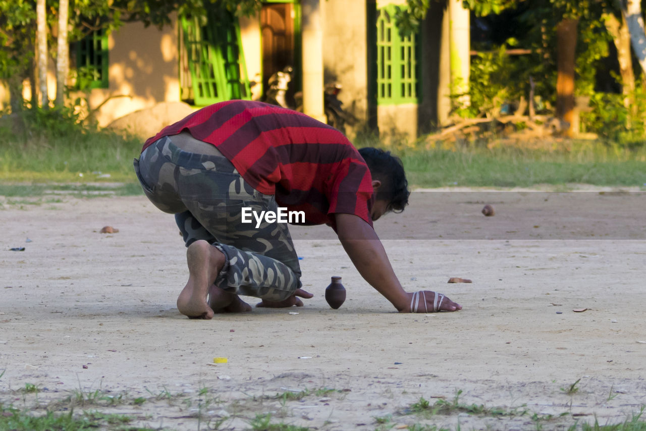 Man bending over spinning top on ground