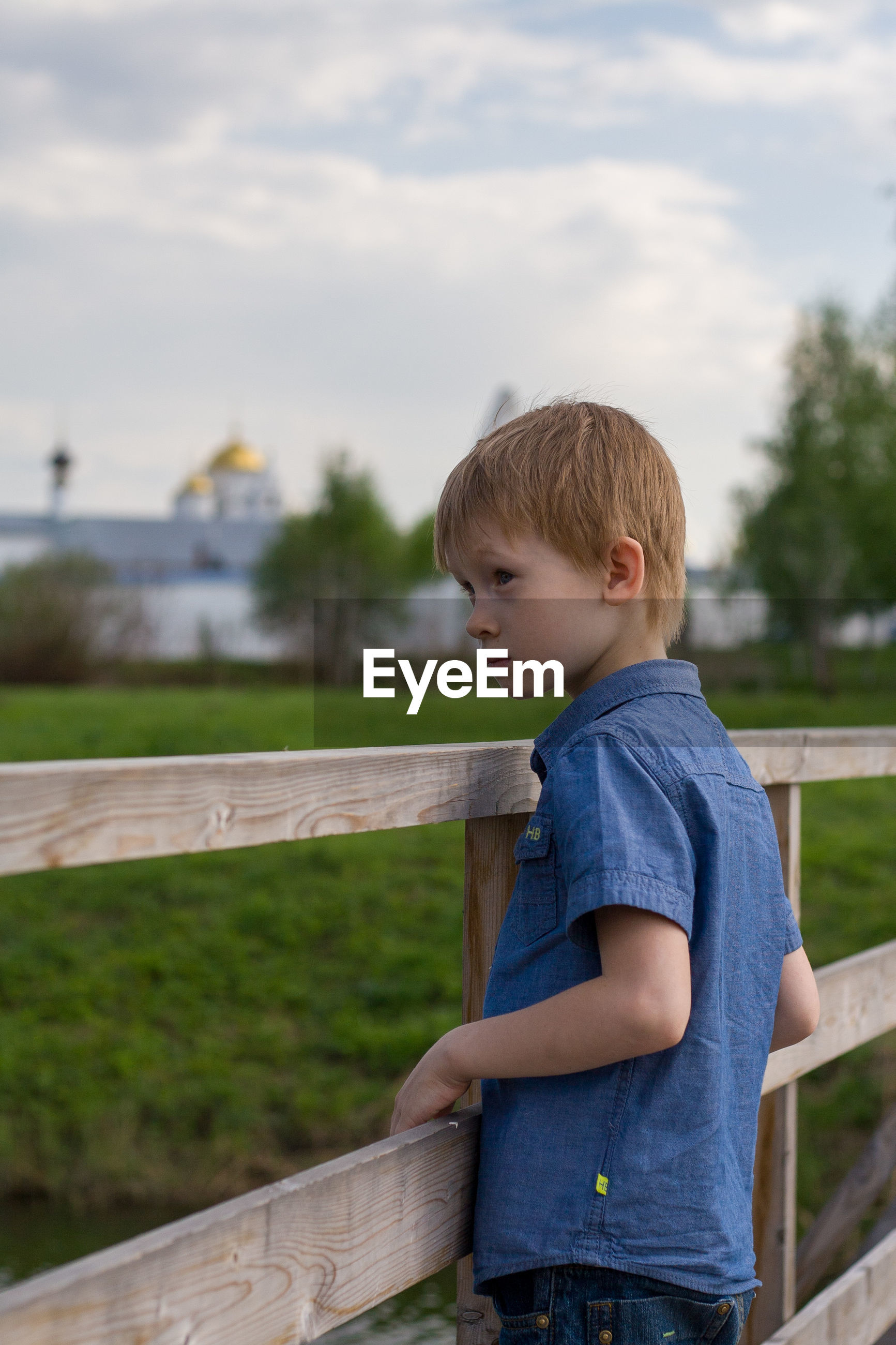 Boy looking away while standing by railing