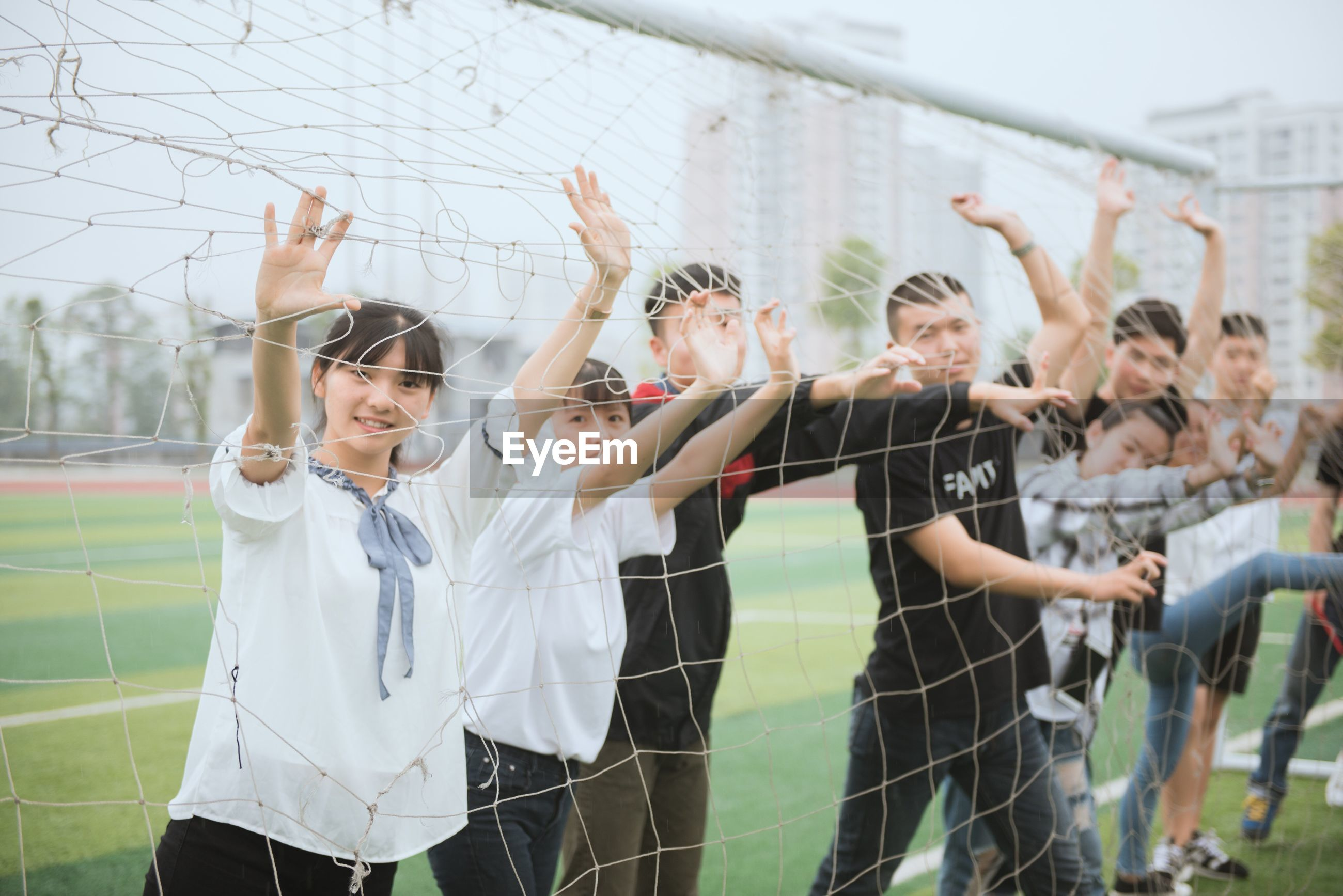 arms raised, real people, teenager, teenage girls, education, standing, togetherness, day, leisure activity, focus on foreground, high school, high school student, learning, outdoors, sport, young women, student, young adult, soccer field, junior high