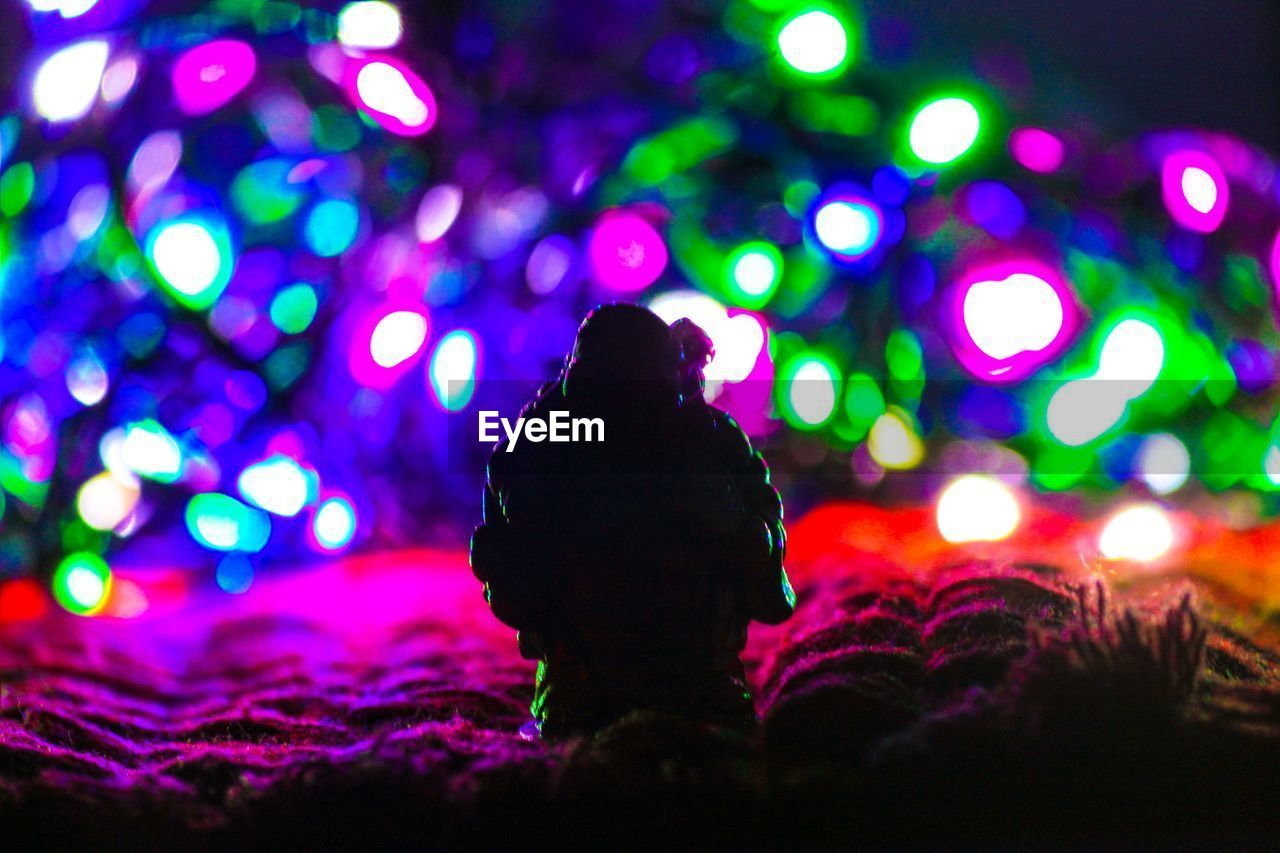 illuminated, night, lighting equipment, multi colored, light - natural phenomenon, glowing, real people, decoration, light, one person, indoors, christmas lights, celebration, lifestyles, focus on foreground, close-up, christmas, leisure activity, electricity