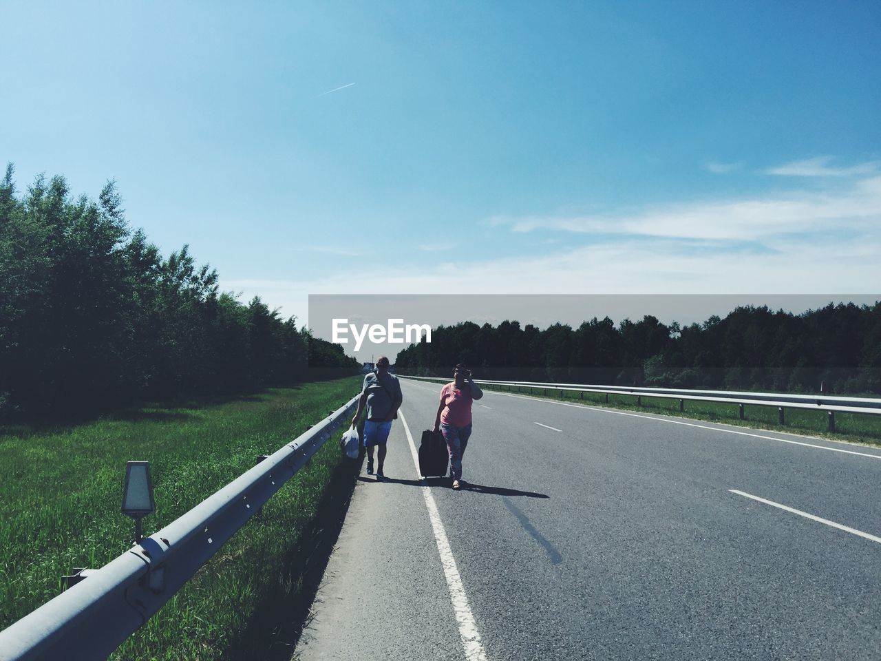 transportation, road, tree, sky, nature, plant, real people, day, women, two people, lifestyles, full length, people, the way forward, rear view, togetherness, adult, direction, men, walking, outdoors, diminishing perspective