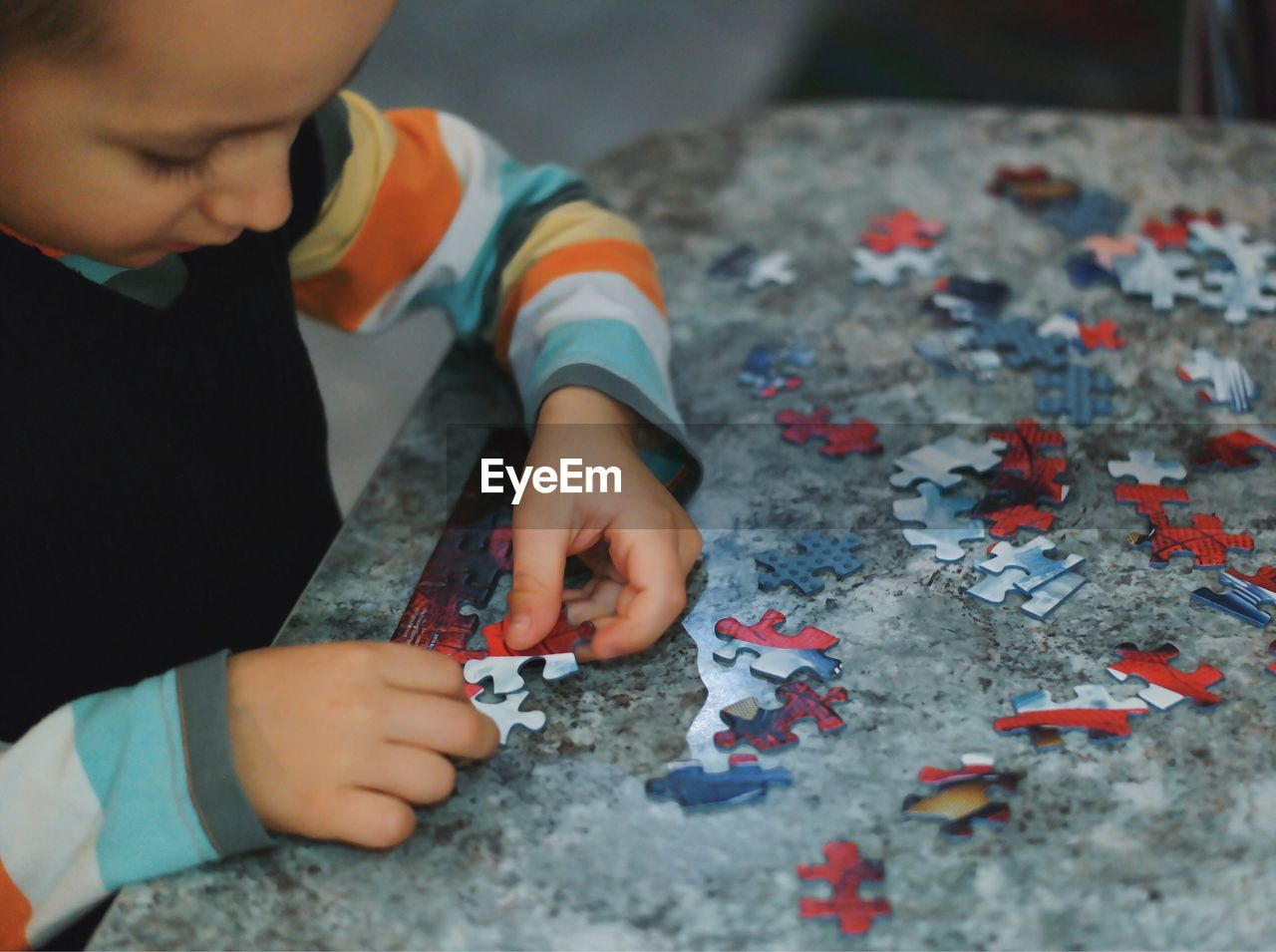 Boy Playing Puzzle Game At Table