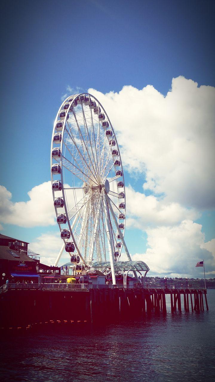 ferris wheel, sky, arts culture and entertainment, water, amusement park, big wheel, cloud - sky, waterfront, no people, outdoors, day, amusement park ride, sea, nature