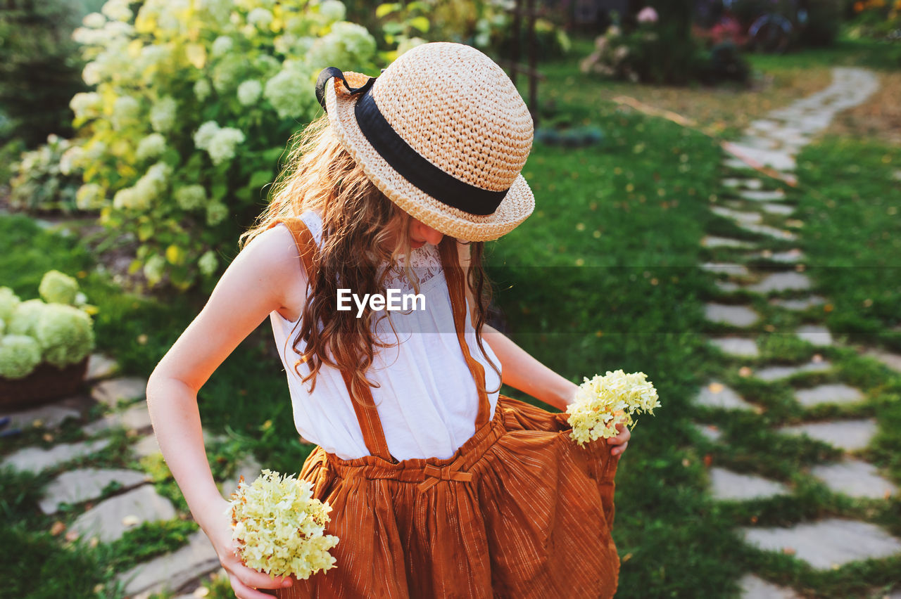 Girl holding flowers while standing in yard