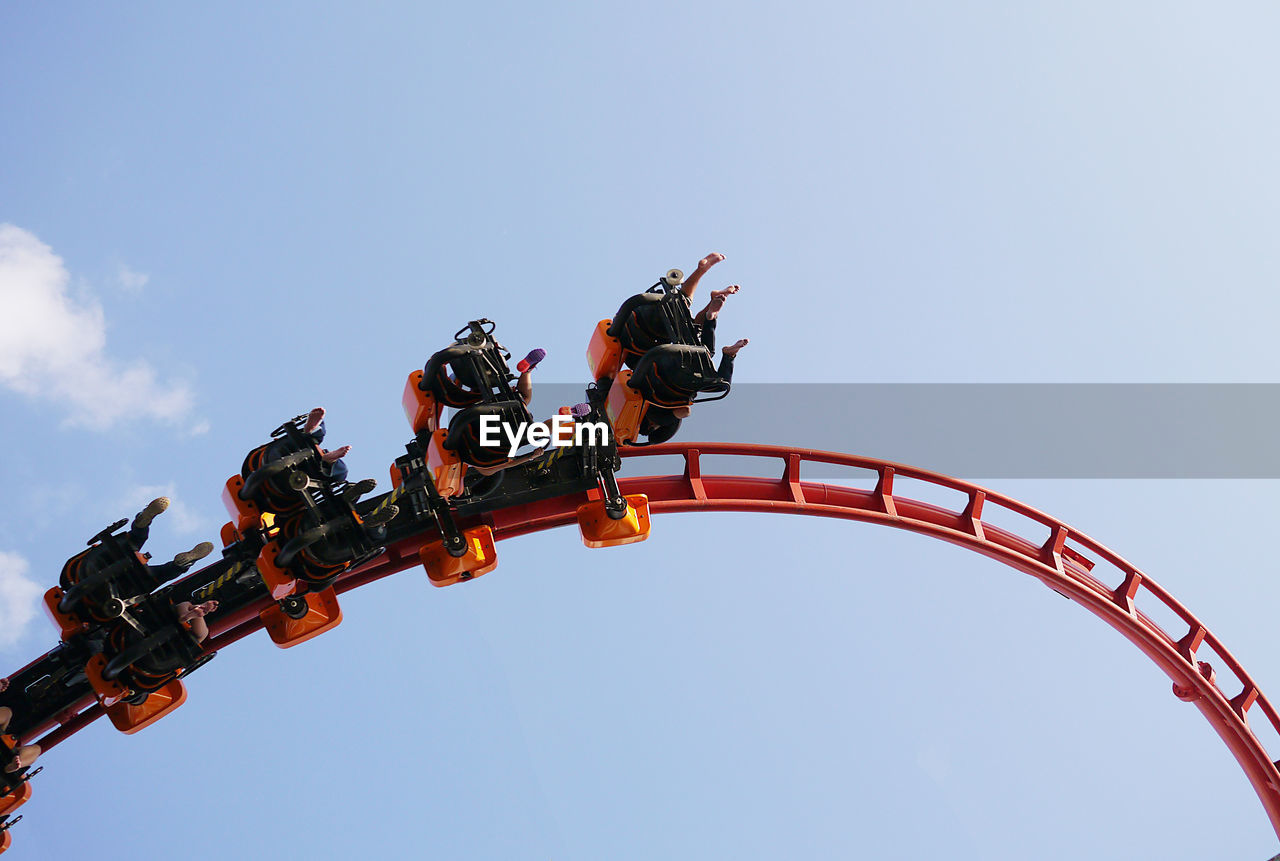 Low Angle View Of People Riding On Rollercoaster Against Sky