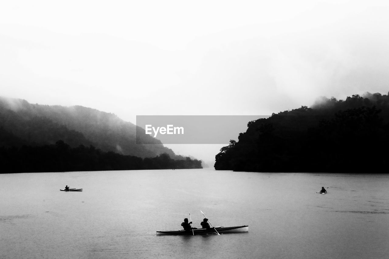 High Angle View Of People Kayaking On Lake Against Clear Sky