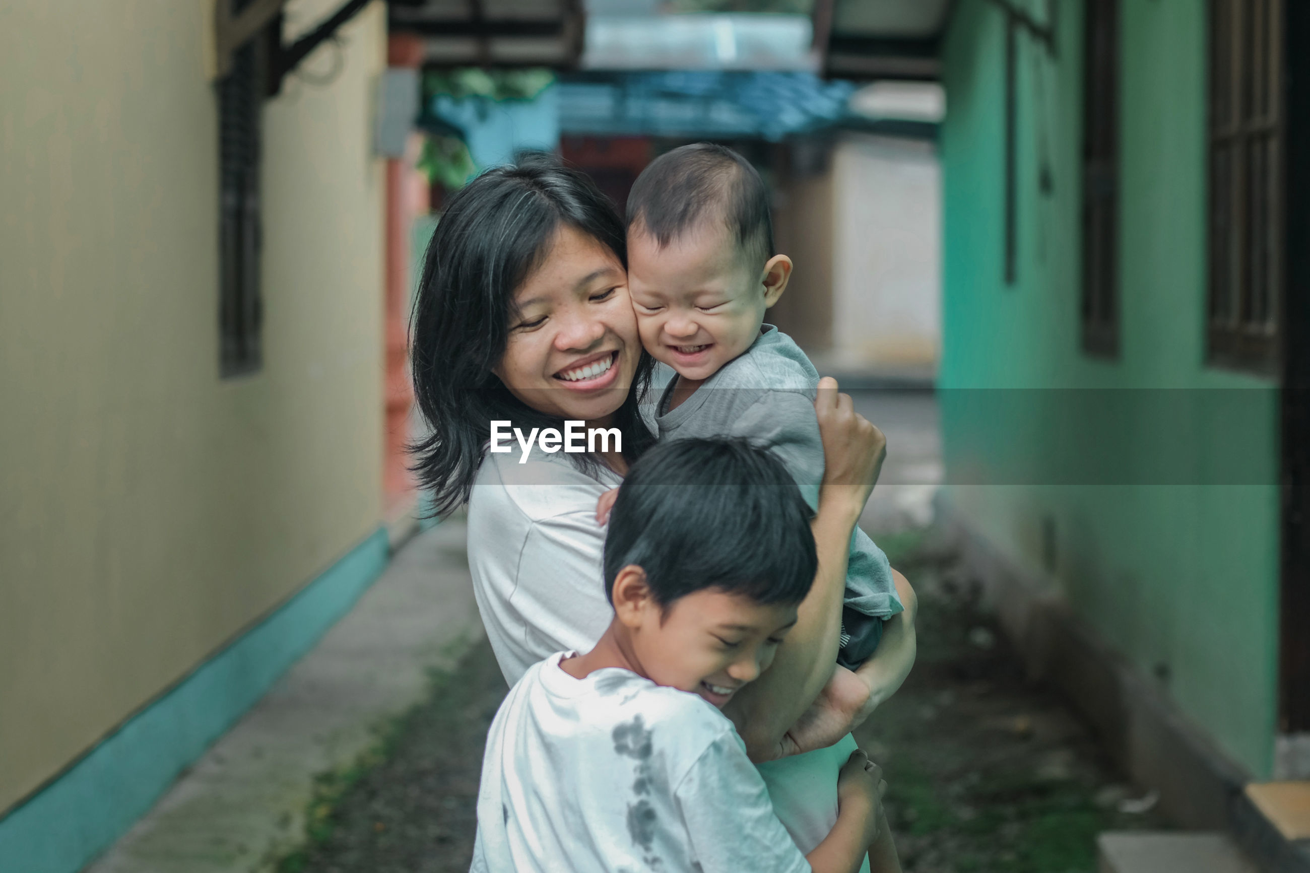 Smiling mother with sons standing outside house