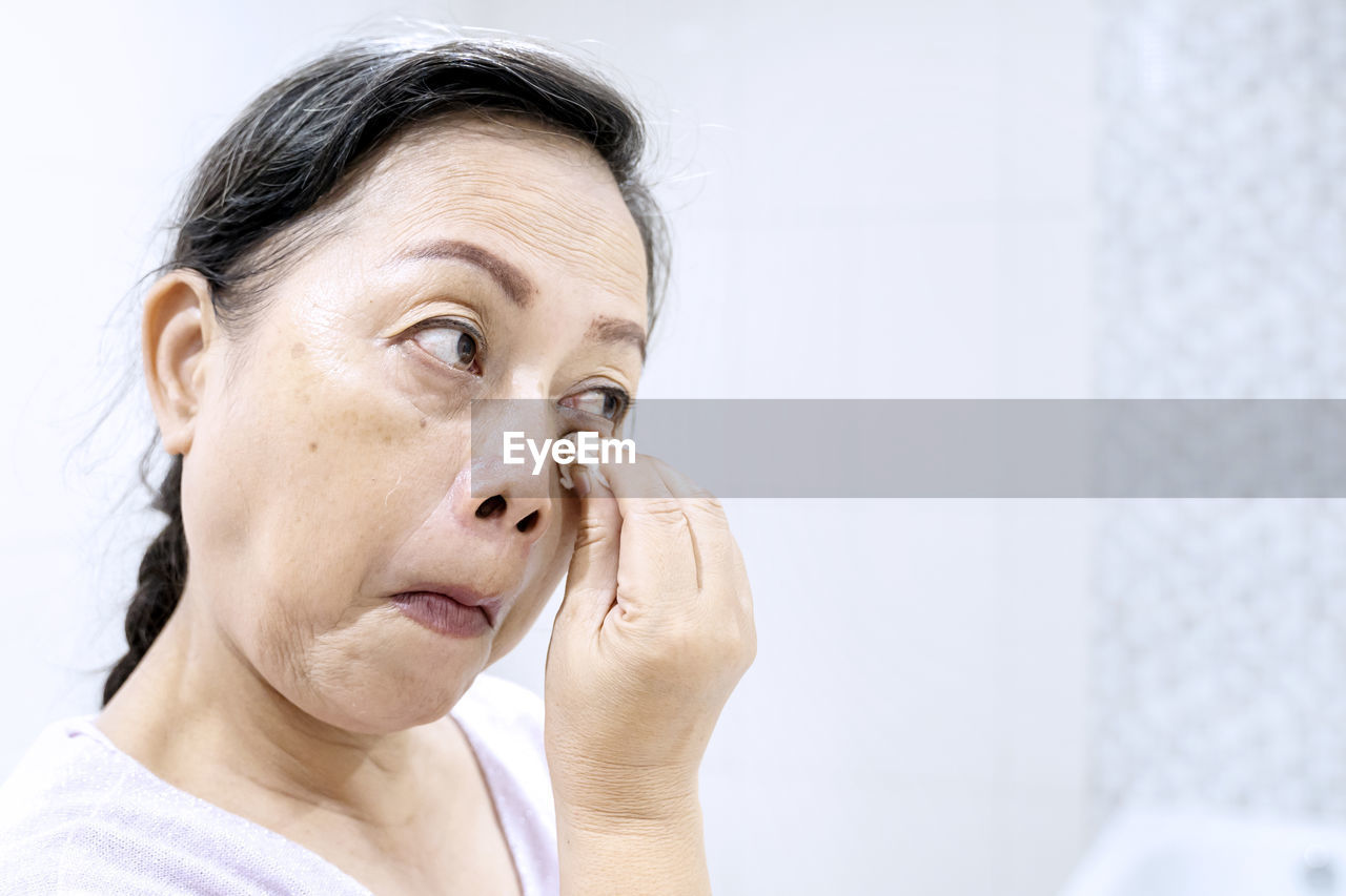 Close-up of senior woman cleaning face against wall