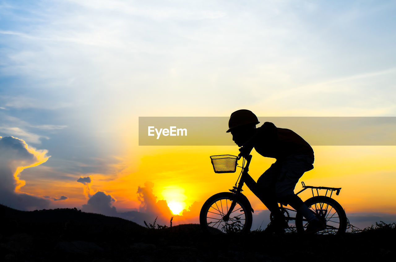 Silhouette Boy Riding Bicycle Against Sky During Sunset