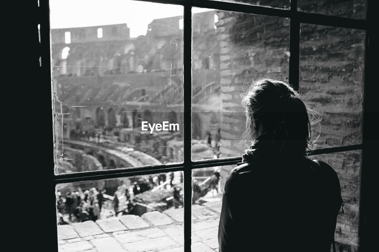 Woman Looking At Coliseum Through Window