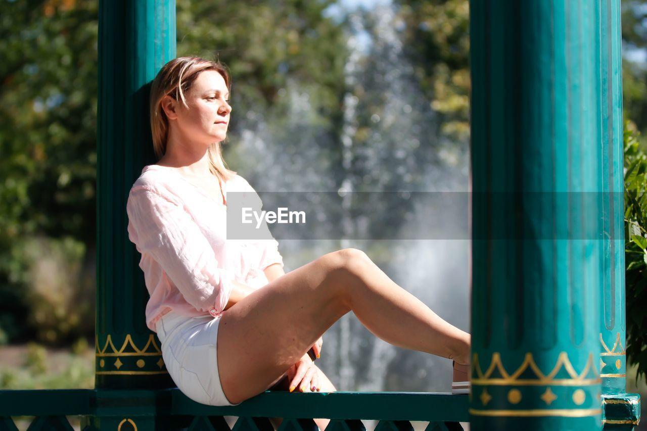 Side view of young woman sitting on railing