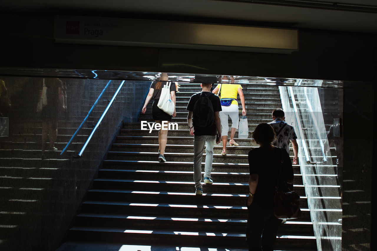 Rear View Of People Climbing On Staircases In City