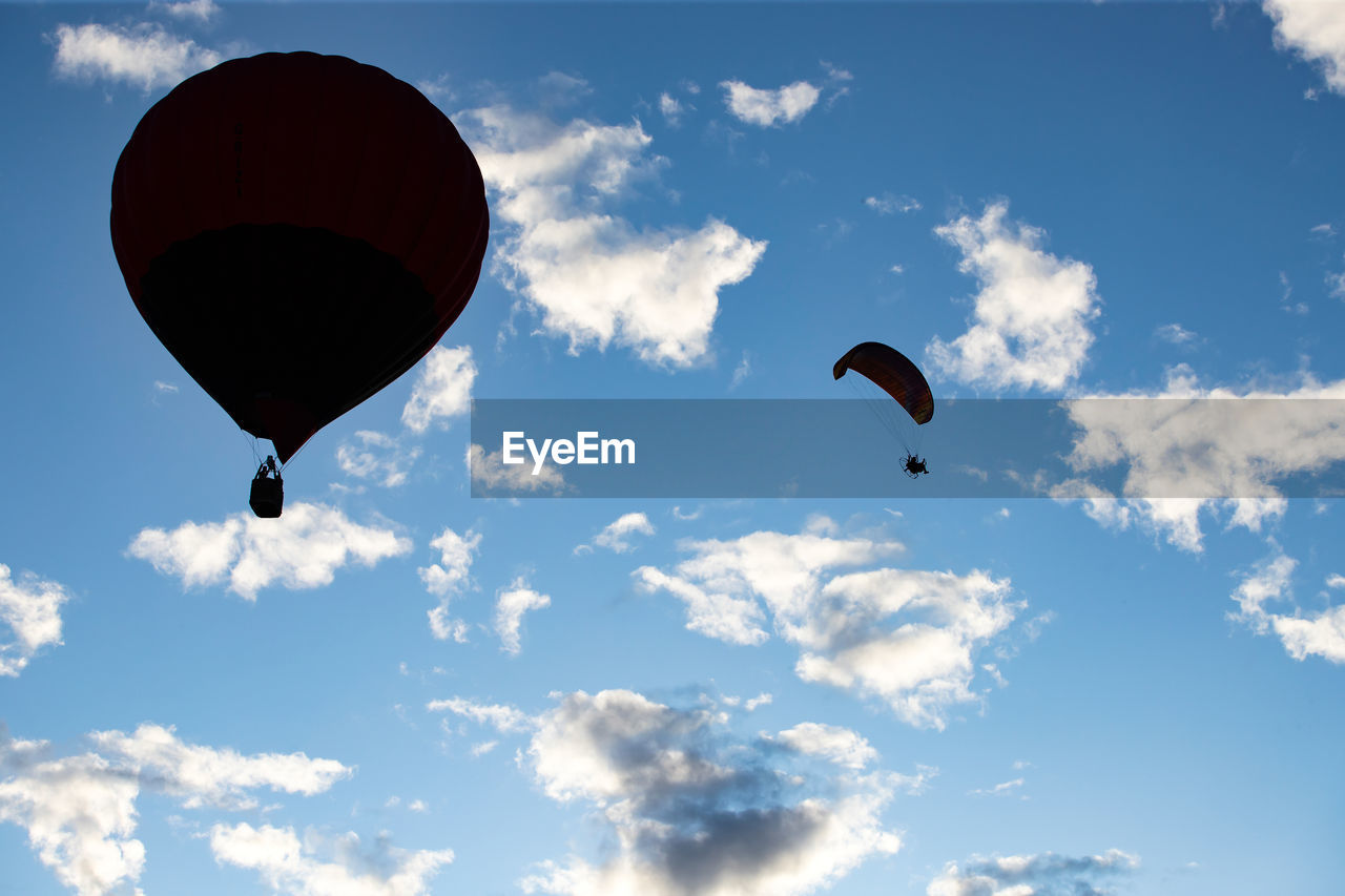 sky, adventure, flying, cloud - sky, low angle view, parachute, mid-air, extreme sports, sport, transportation, paragliding, unrecognizable person, exhilaration, freedom, day, leisure activity, joy, nature, real people, outdoors, parasailing