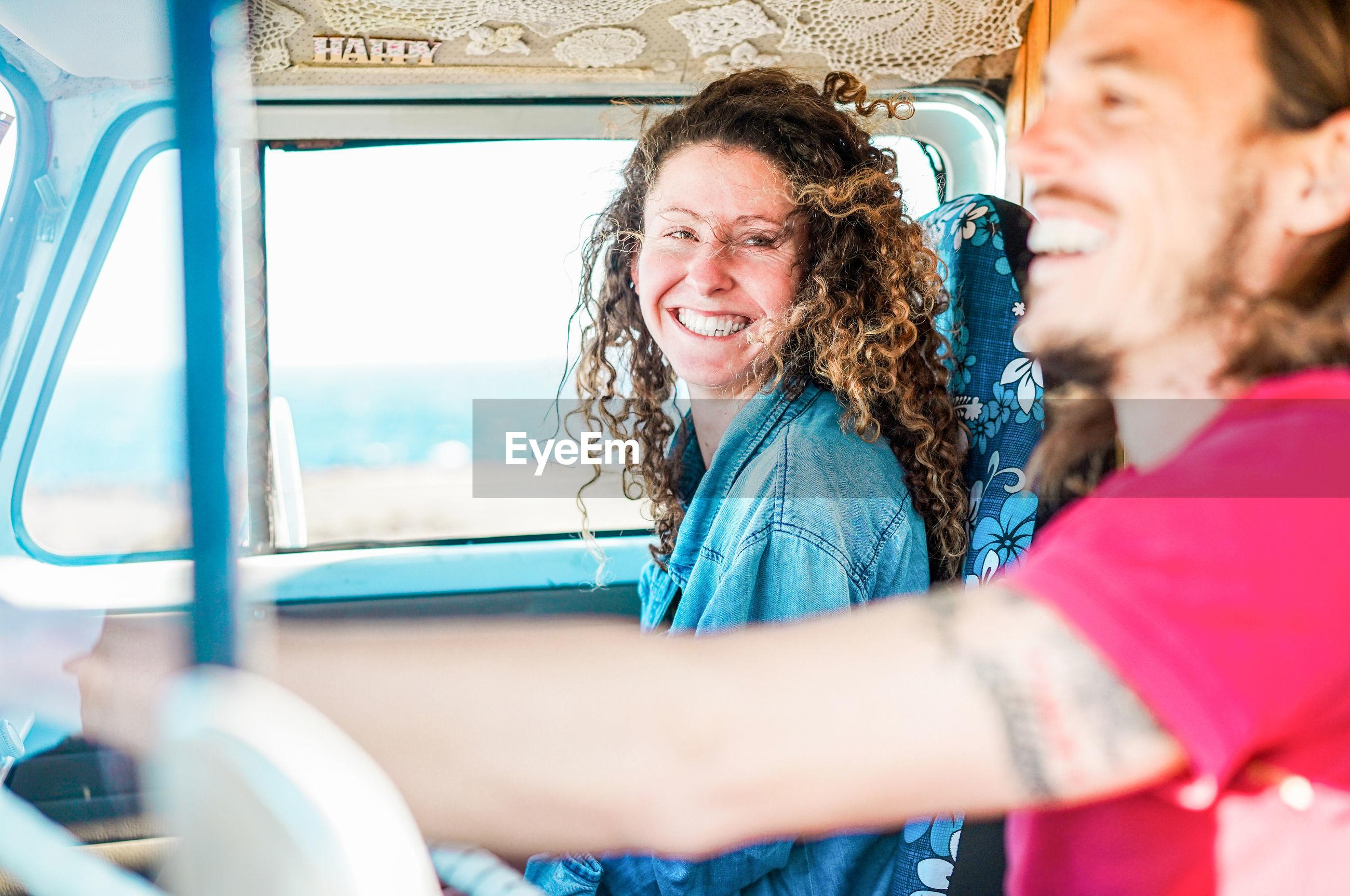 Cheerful couple traveling in van