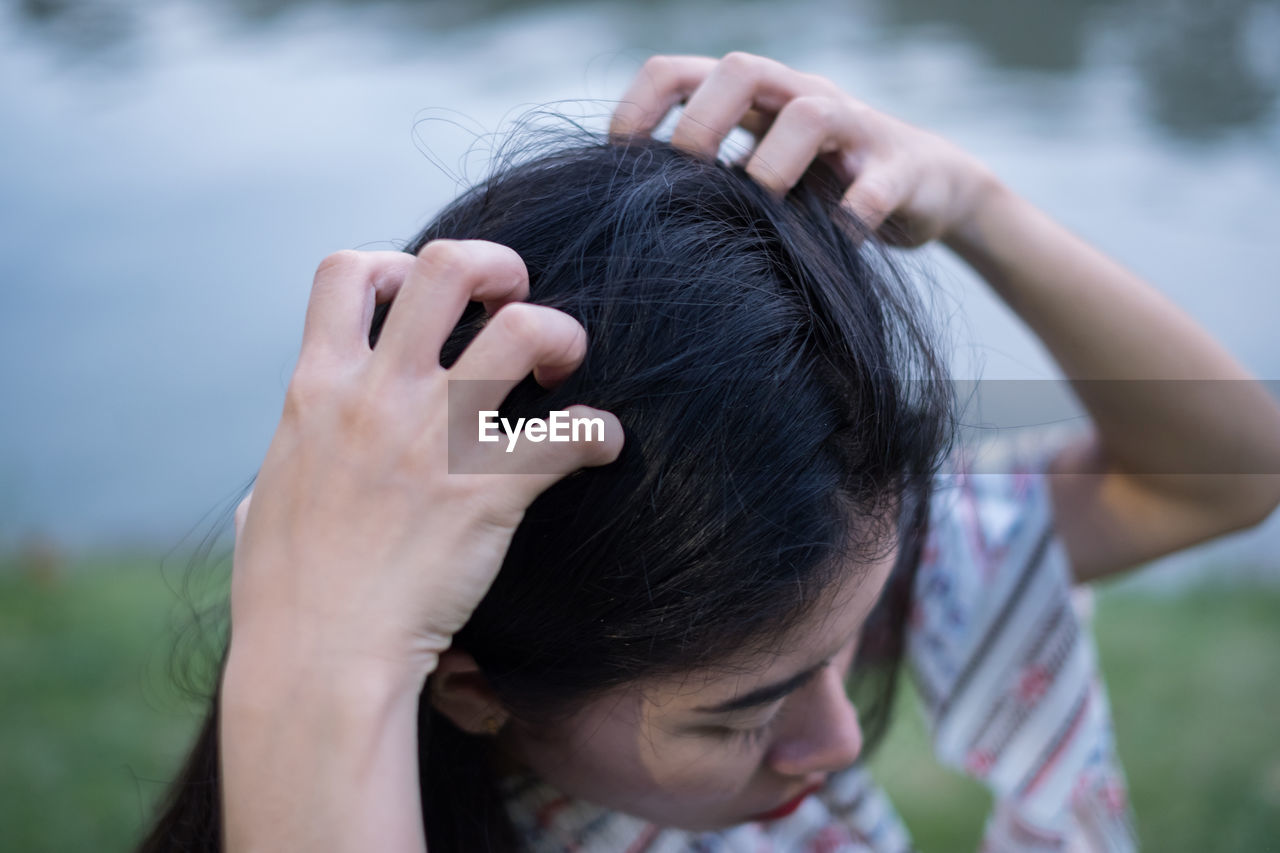 Close-up of woman scratching head by lake in park