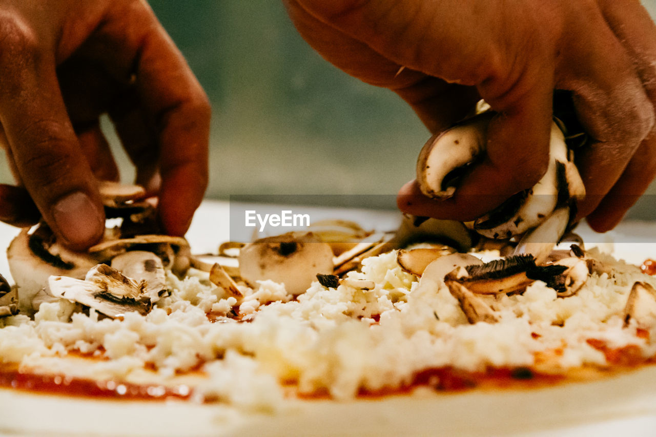 Cropped hands of man garnishing pizza
