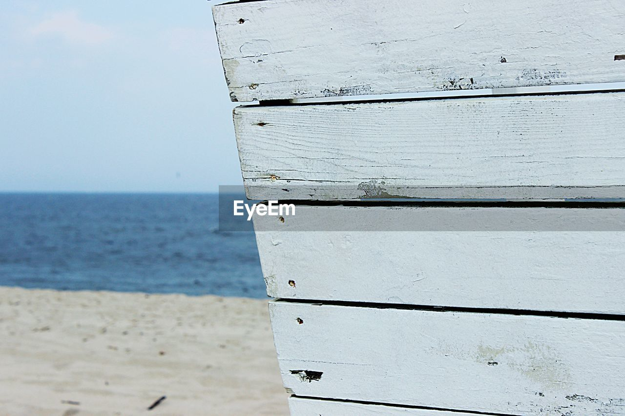 Close-Up Of Wooden Post On Beach Against Sky