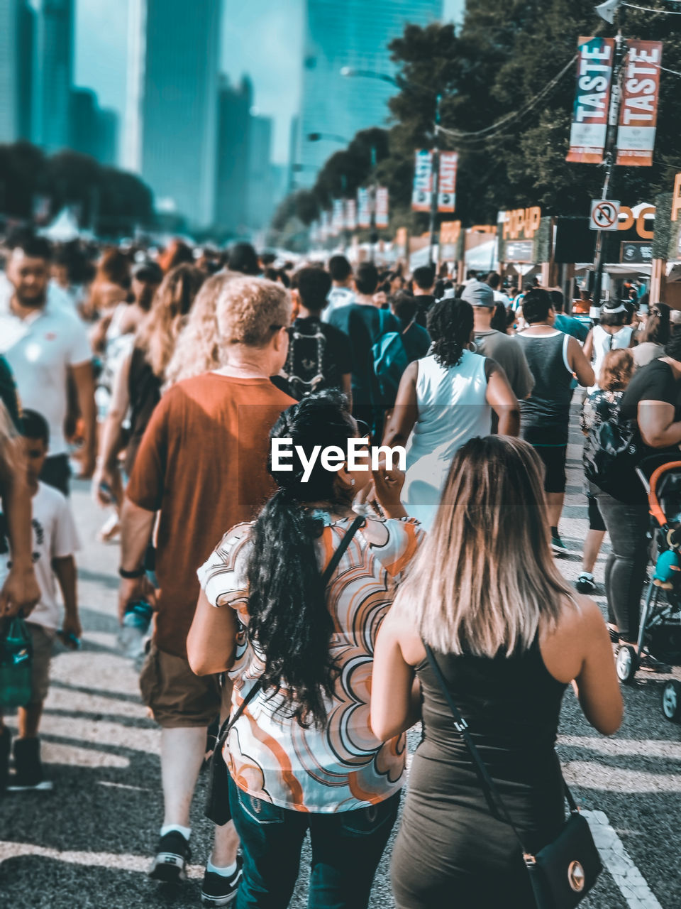 city, real people, crowd, group of people, architecture, street, large group of people, lifestyles, men, women, built structure, adult, city life, leisure activity, day, casual clothing, togetherness, road, rear view, hairstyle