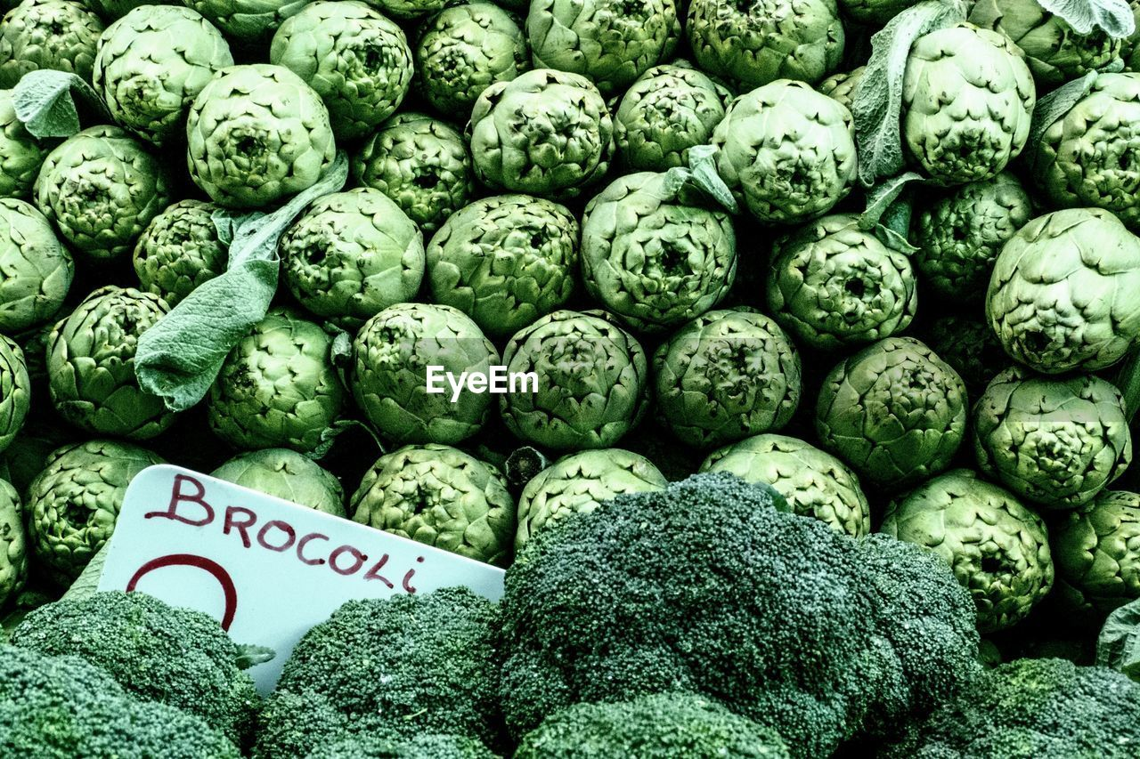 Full frame shot of fresh artichokes and broccolis with label at market stall