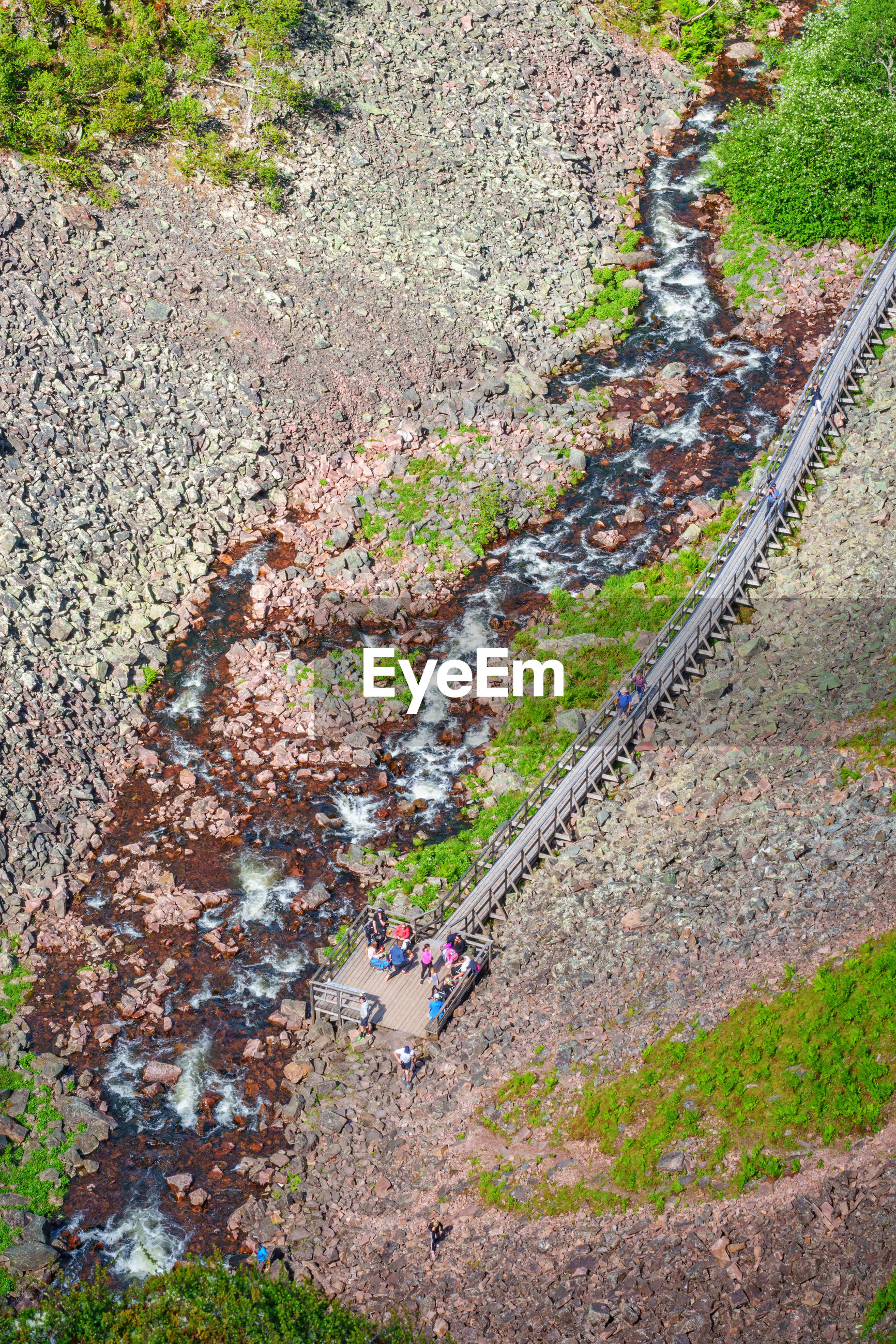 HIGH ANGLE VIEW OF PEOPLE WALKING ON FOOTPATH BY MOUNTAIN