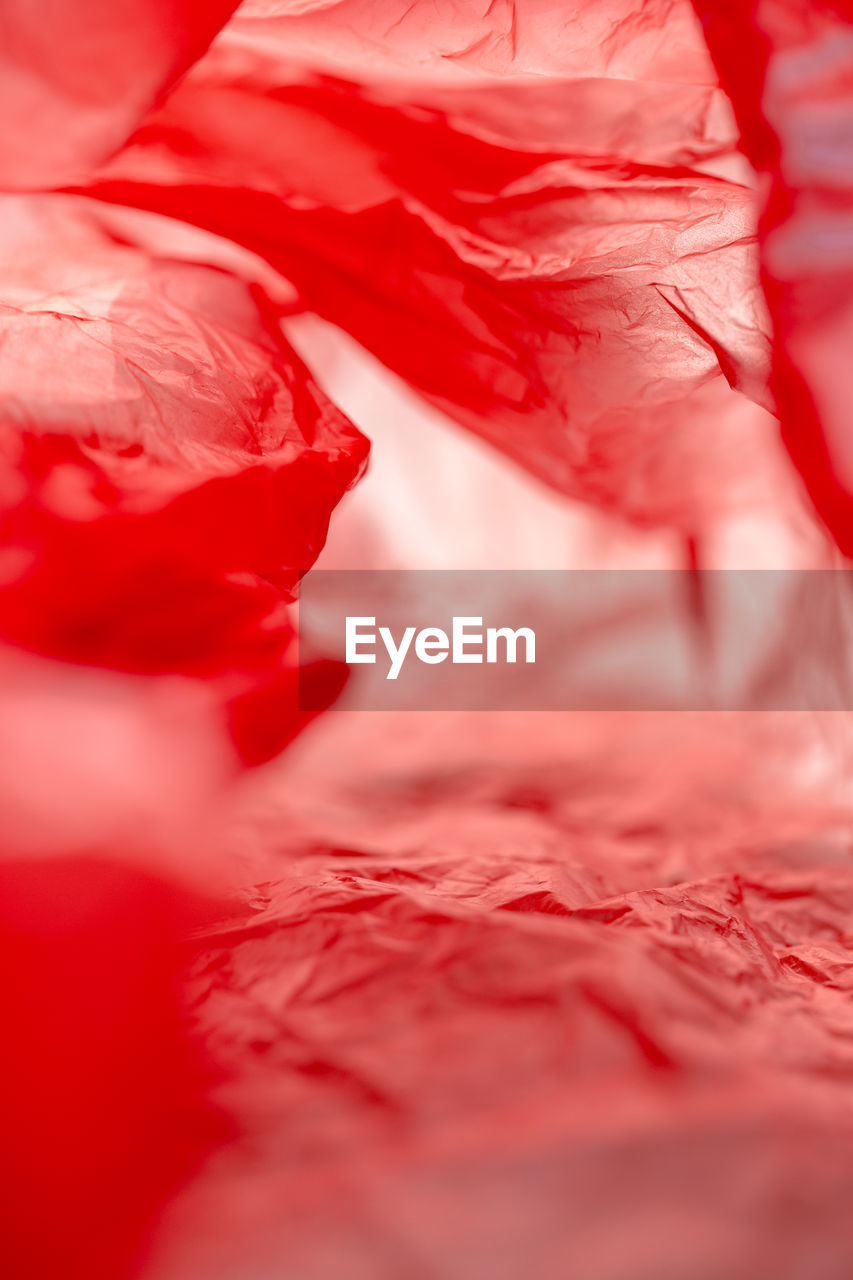 red, close-up, no people, selective focus, full frame, backgrounds, indoors, textile, pattern, freshness, beauty in nature, still life, textured, petal, nature, extreme close-up, crumpled, abstract, day