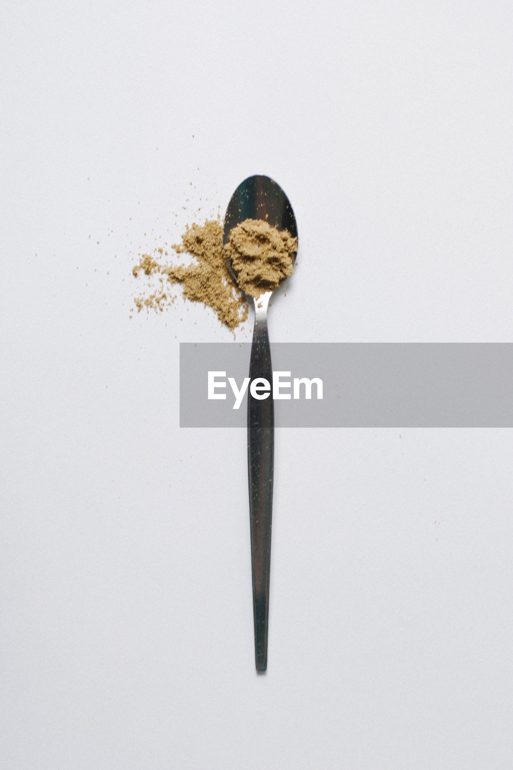 High angle view of ingredient in spoon over white background