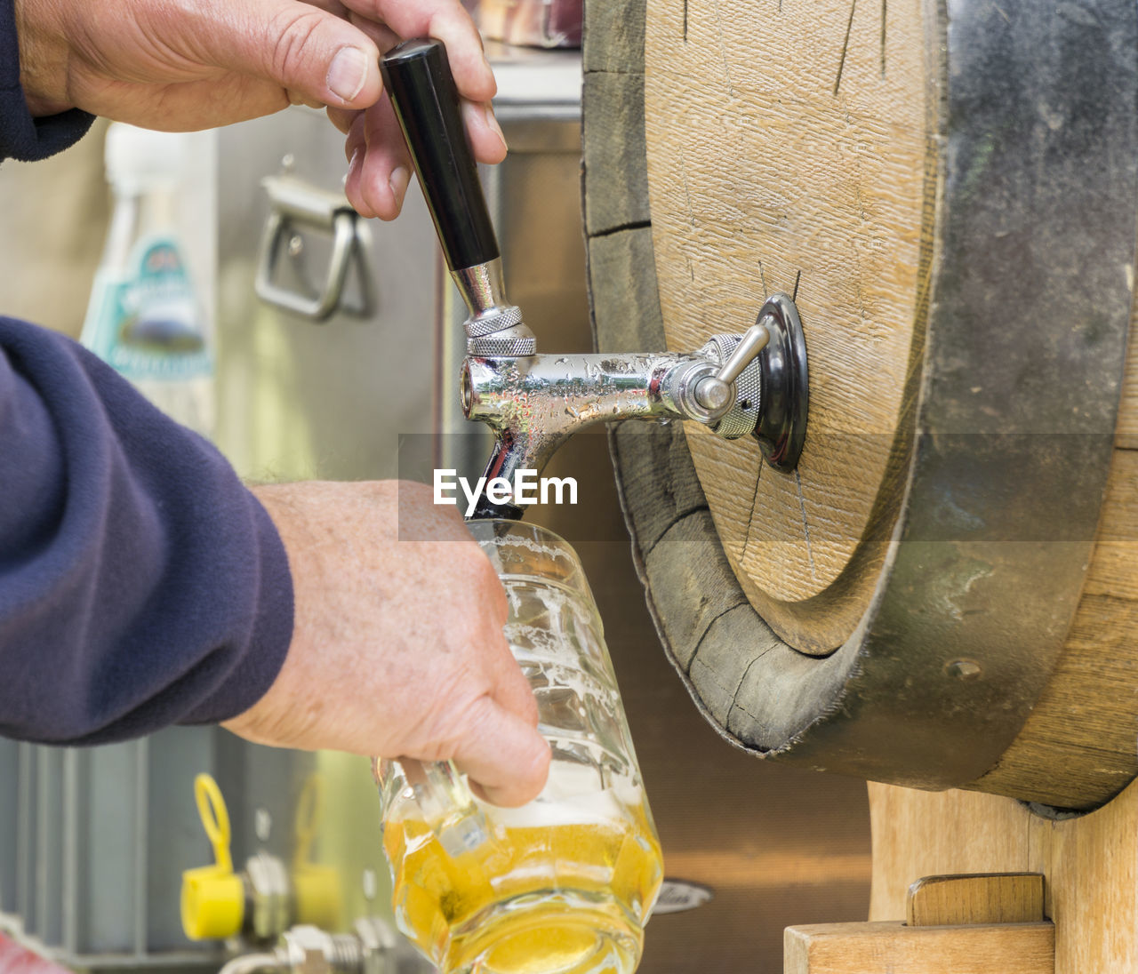 Close-Up Of Hands Pouring Beer From Barrel