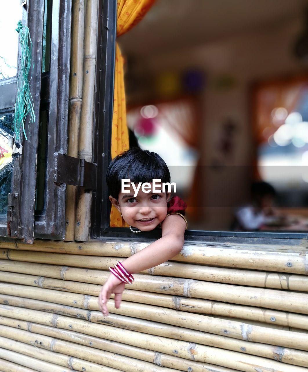 Portrait Of Cute Girl Leaning On Window