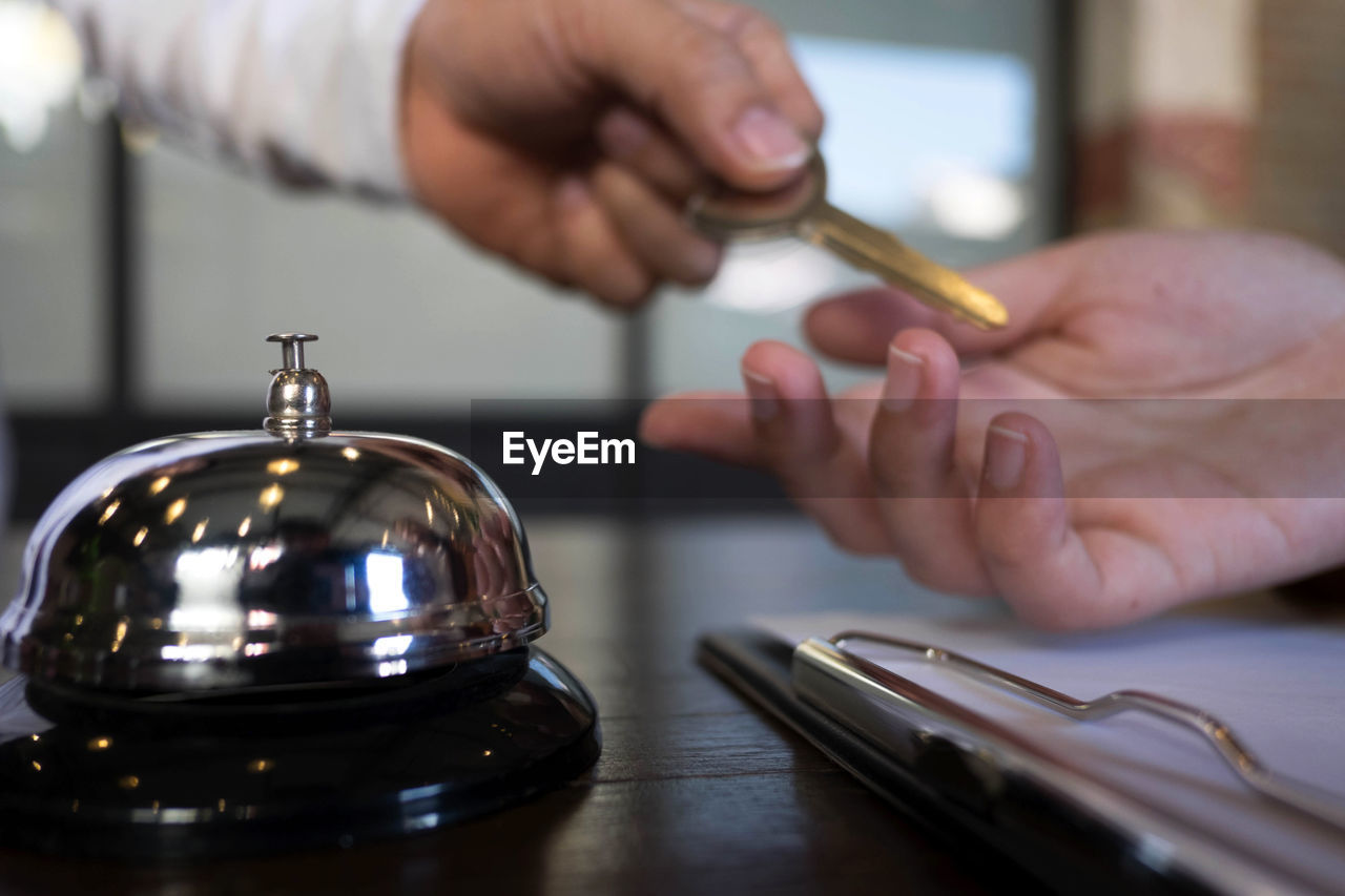 Cropped hand of real estate agent giving house key to customer by service bell on desk