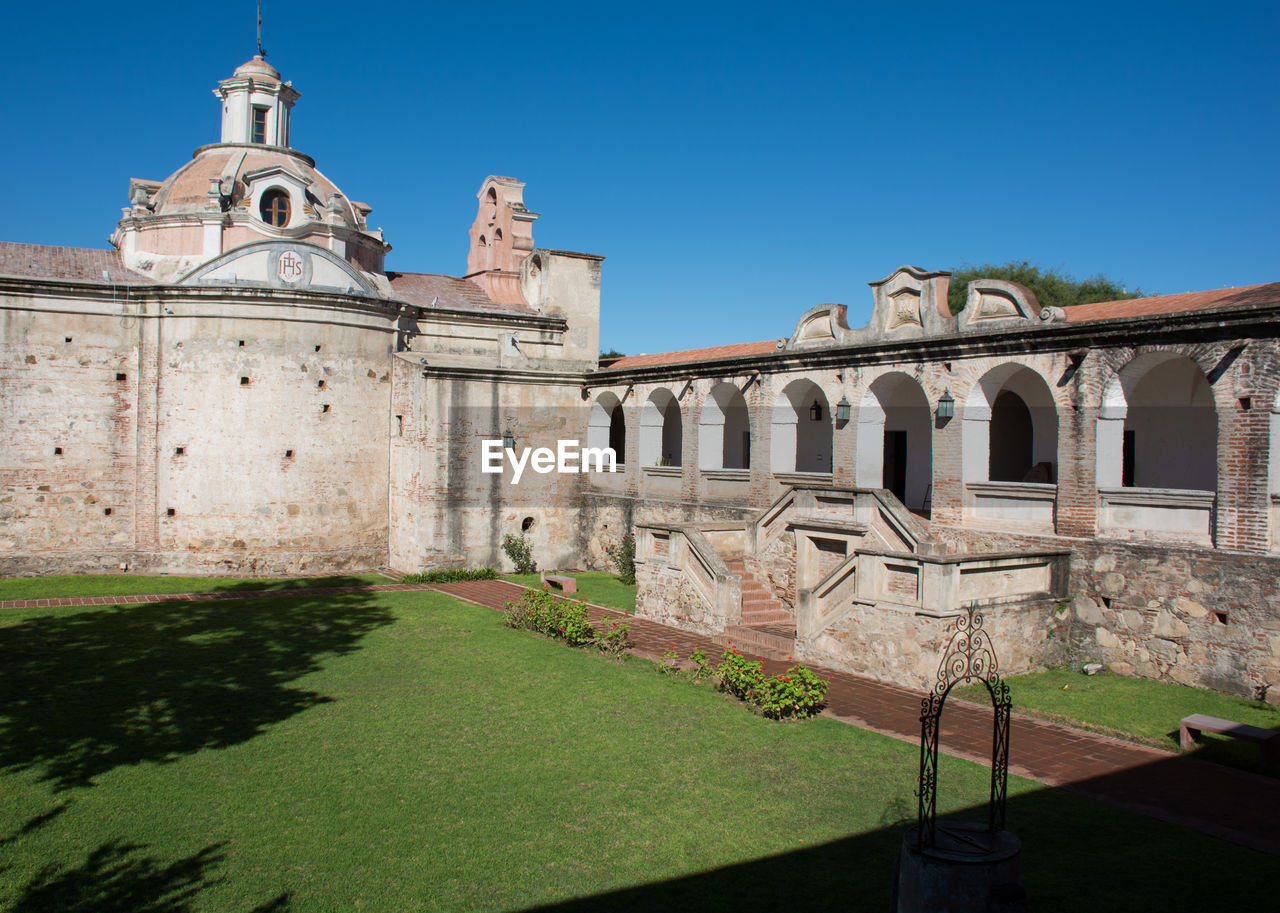 architecture, built structure, building exterior, sky, history, the past, nature, grass, day, building, clear sky, blue, plant, travel destinations, sunlight, place of worship, religion, belief, arch, ancient, no people, outdoors, courtyard, ancient civilization