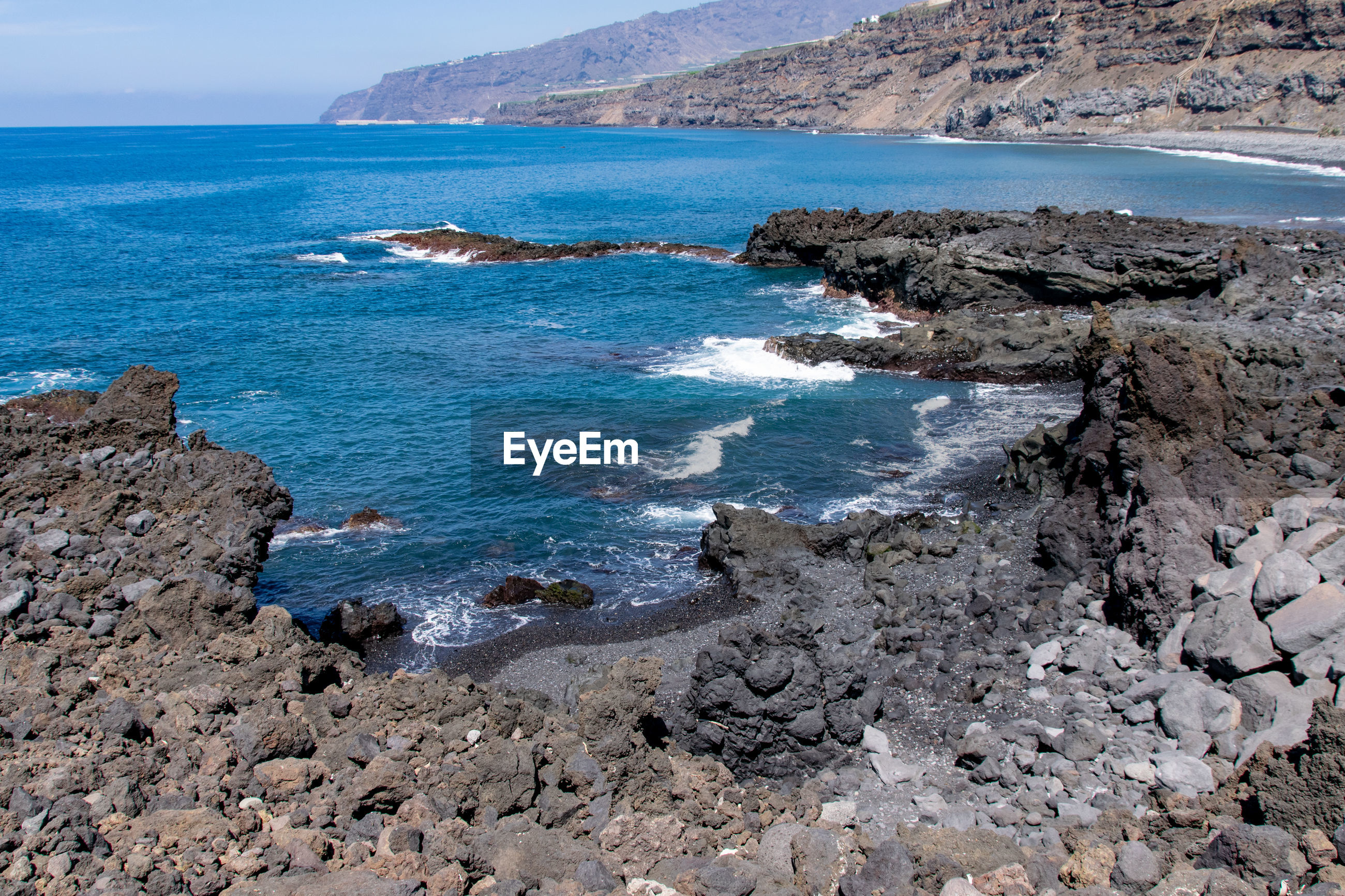 Edge of volcanic lava field meeting atlantic ocean at playa los guirres, la palma, canary islands