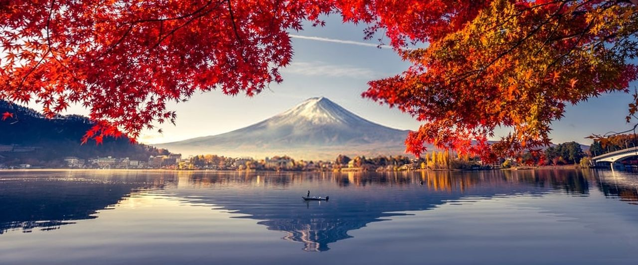 Reflection of snowcapped volcano in lake during autumn