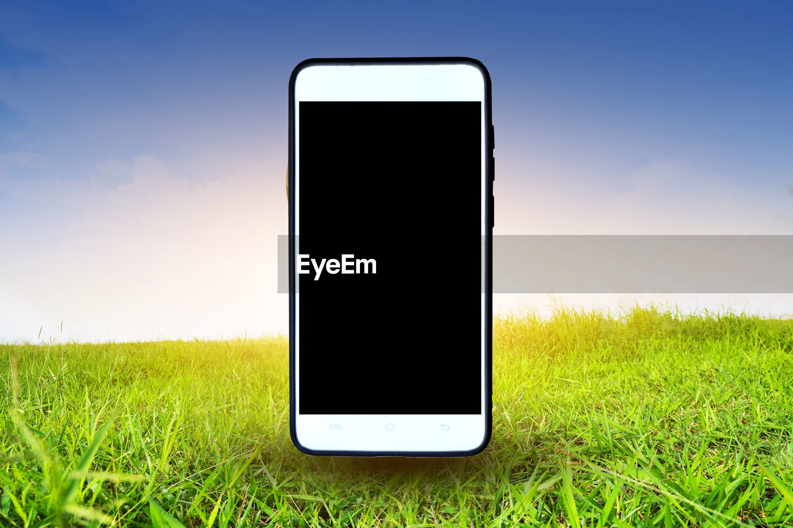 Digital composite image of mobile phone on grassy field against sky