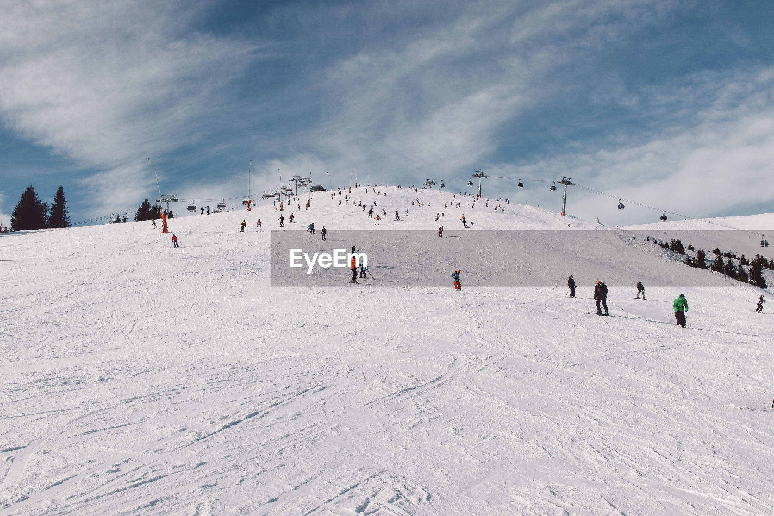 Tourists skiing on snow covered mountain against sky