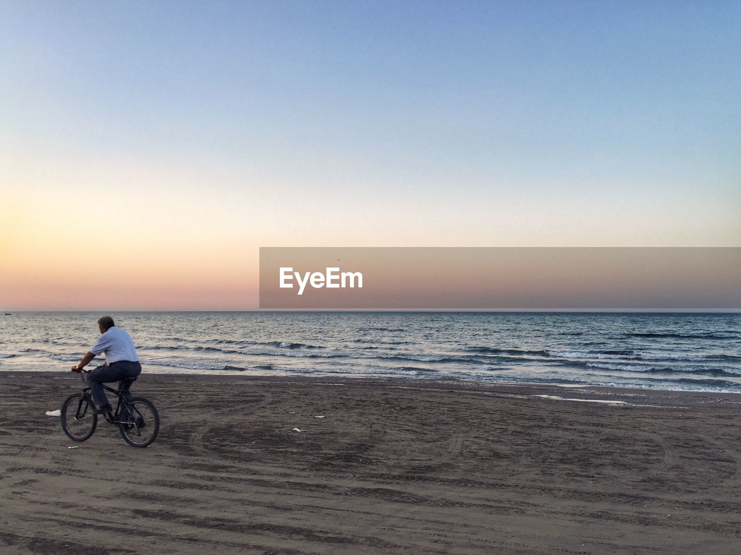 MAN WITH BICYCLE ON BEACH AGAINST SKY DURING SUNSET